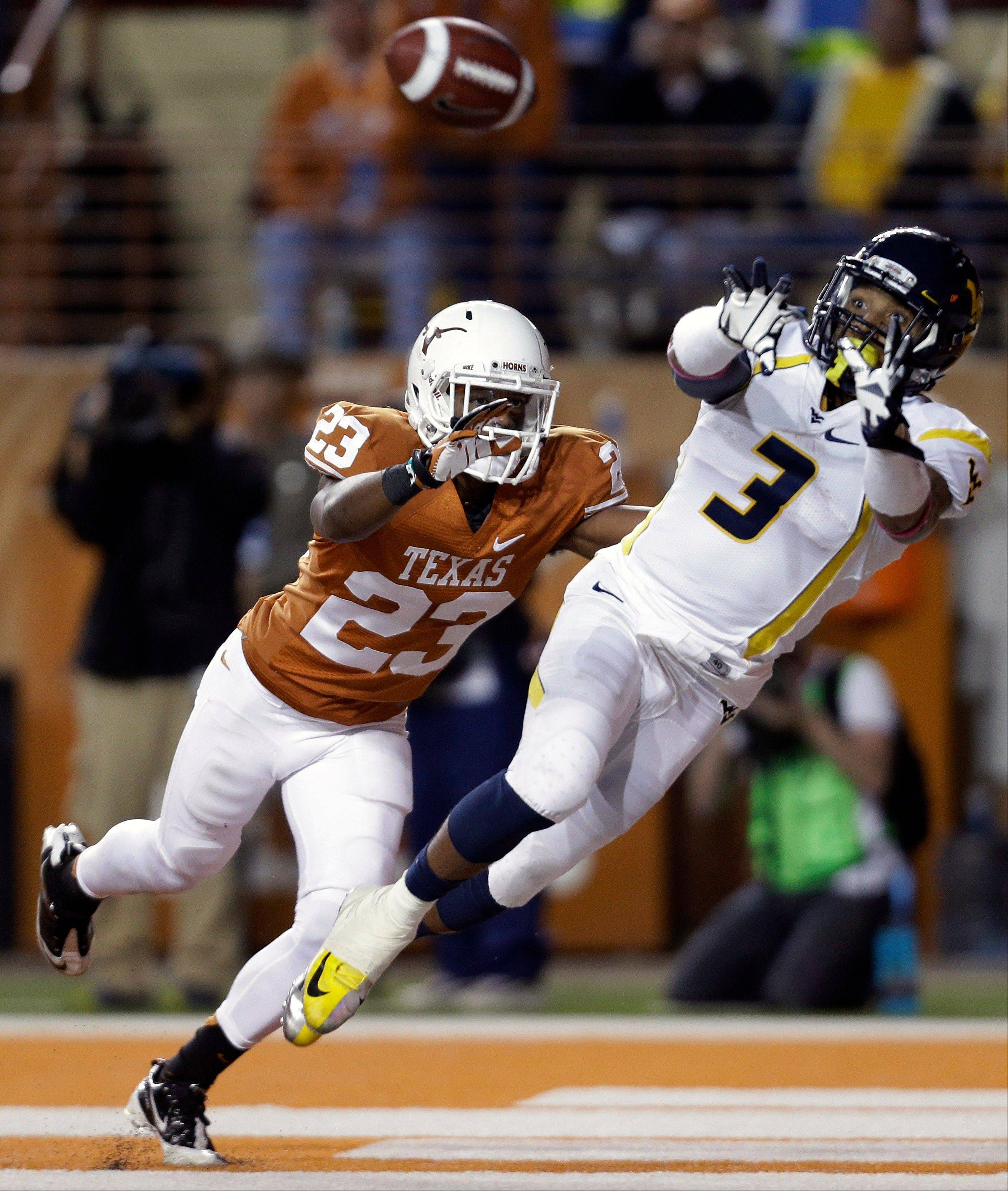 West Virginia's Stedman Bailey leaps for a touchdown pass as Texas' Carrington Byndom defends during the third quarter Saturday in Austin, Texas.