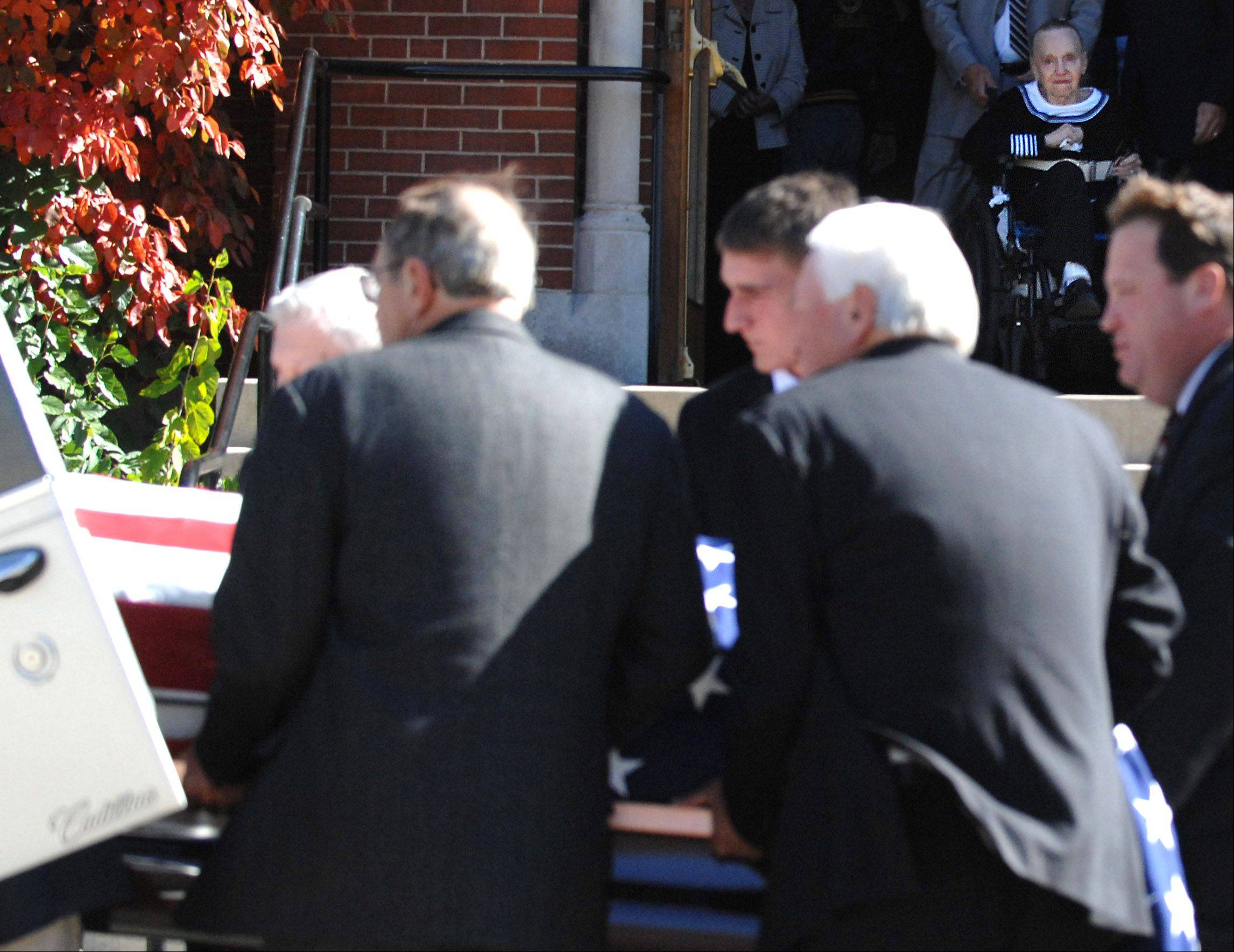 Theresa Kudlicki watches as the casket holding her husband, Robert, is placed in a hearse following his funeral at St. Charles Borromeo Catholic Church in Hampshire Monday. Robert Kudlicki was a two-term mayor of Hampshire and two-term Kane County Board member. The Kudlickis celebrated their 59th wedding anniversary in August.