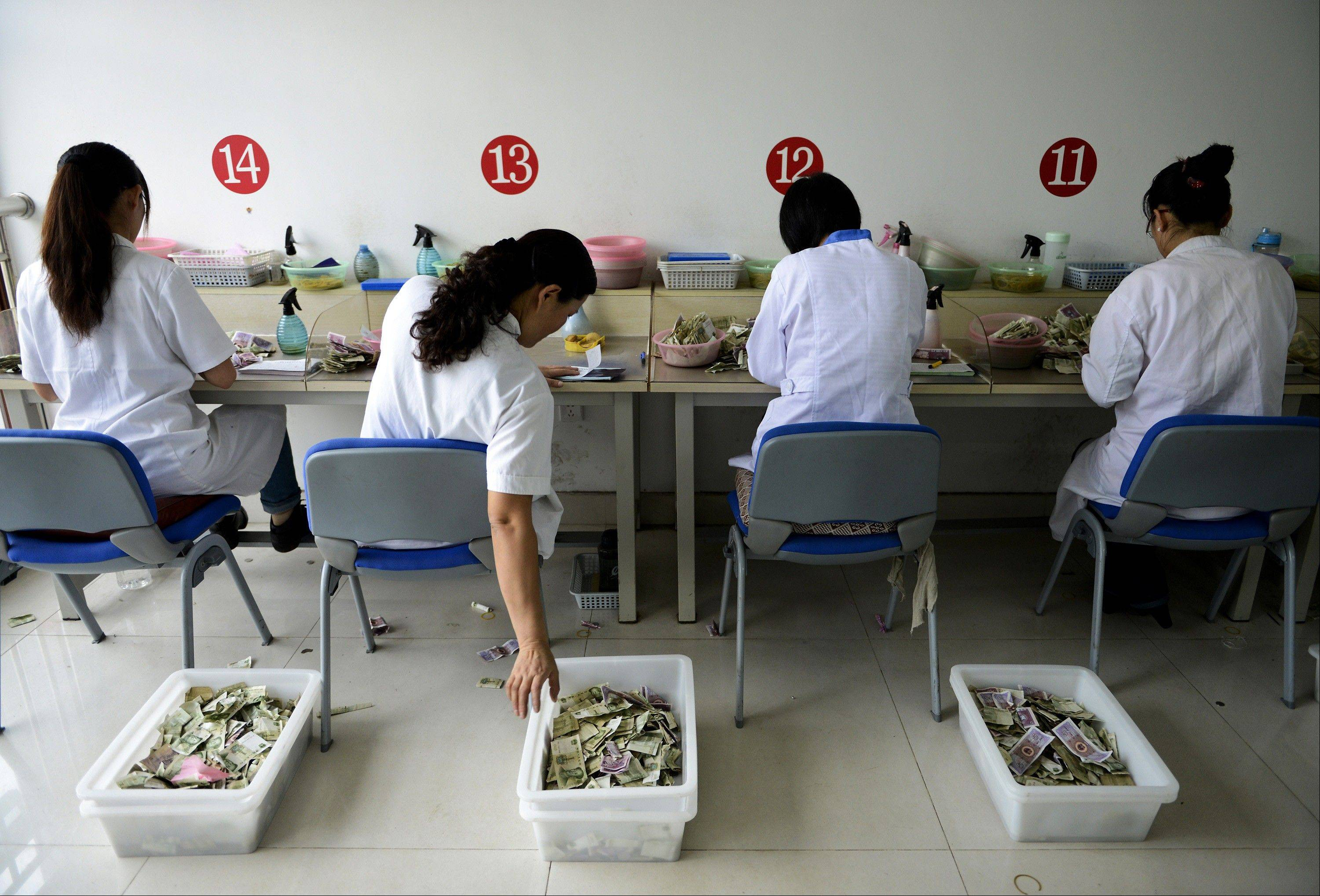 Workers count the small currency notes from bus fares at the accounting center of a bus company in Rizhao city in east China's Shandong province.