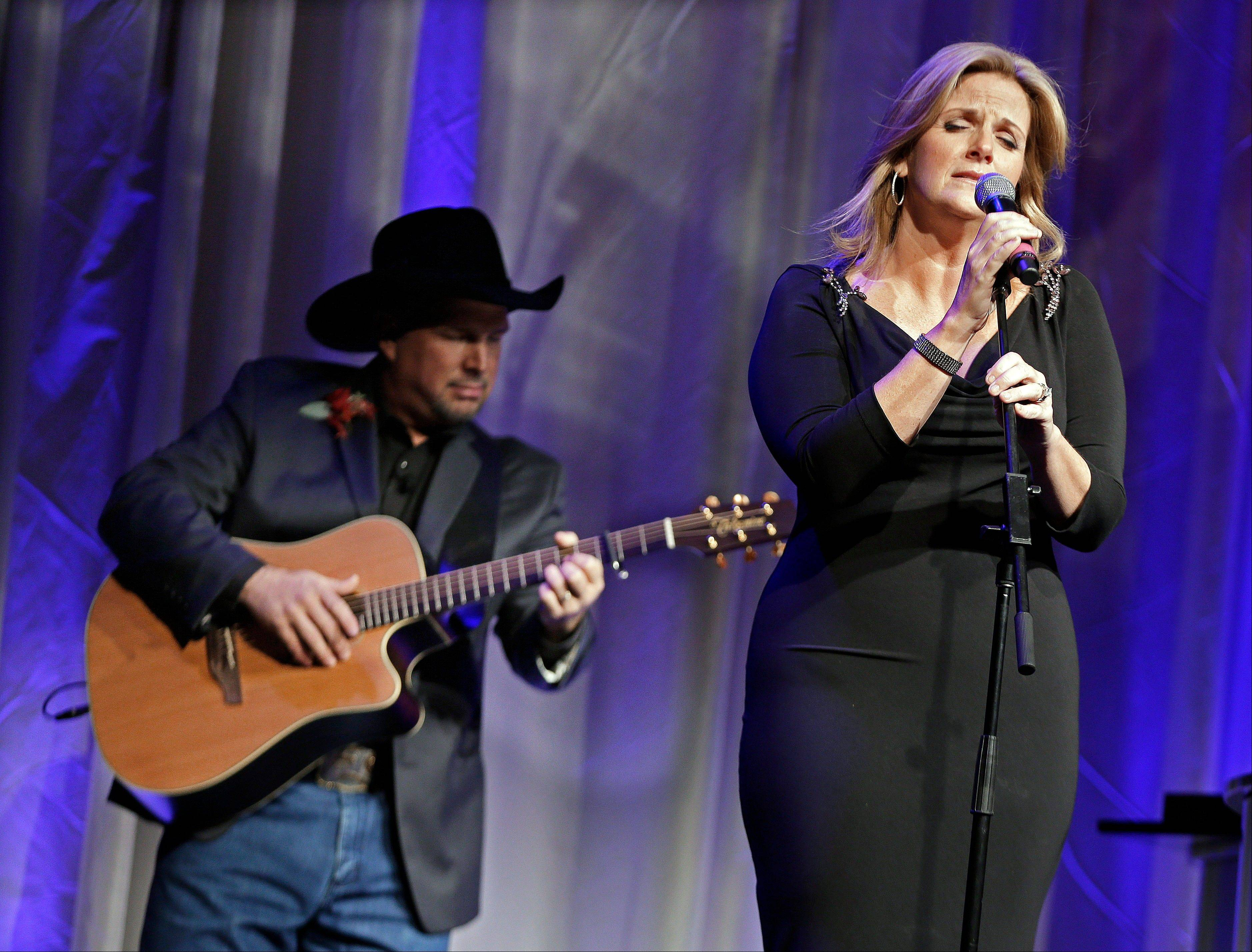 "Trisha Yearwood is accompanied by her husband, Garth Brooks, as she sings ""Wind Beneath My Wings,"" a song written by Larry Henley, as Henley was inducted into the Nashville Songwriters Hall of Fame on Sunday."
