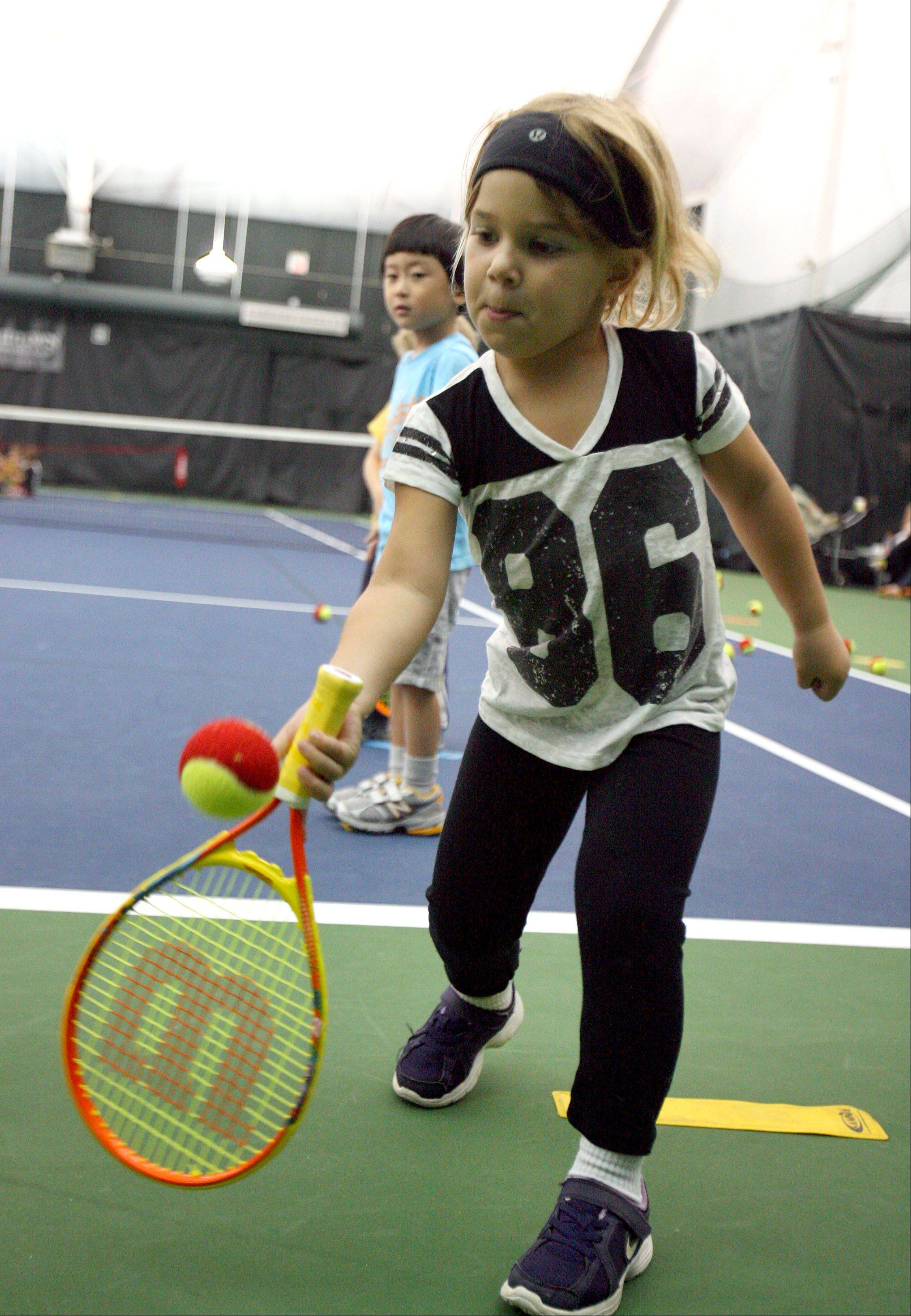 Julia Jacobson, 4, of Riverwoods hits the ball during the Midtown Athletic Club's Tennis Explorers class in Bannockburn. The program blends physical activities, tennis skills and storytelling in an on-court environment.