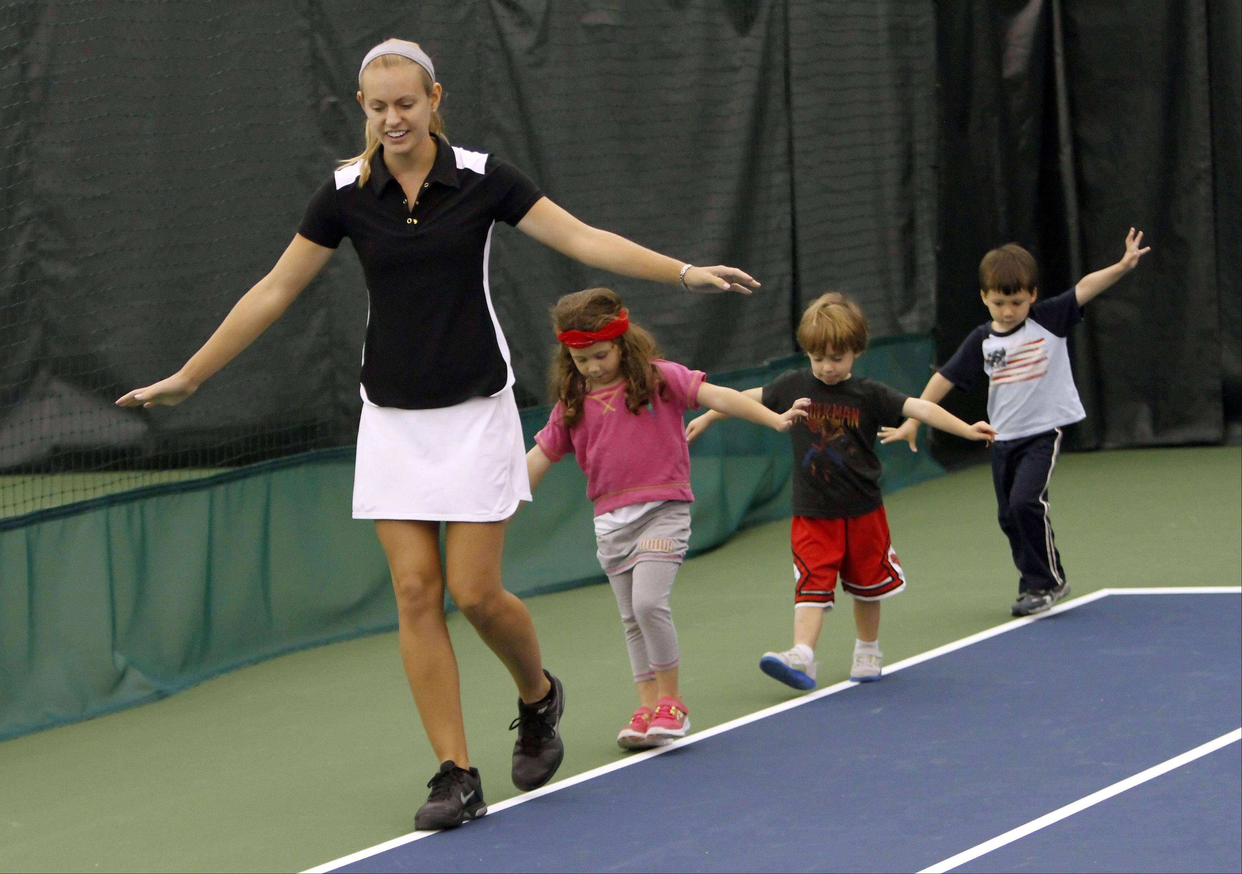Instructor Blair McCarty leads kids on a balance drill during Midtown Athletic Club's tennis program for toddlers in Bannockburn. Tennis Explorers blends physical activities, tennis skills and storytelling in an on-court environment.