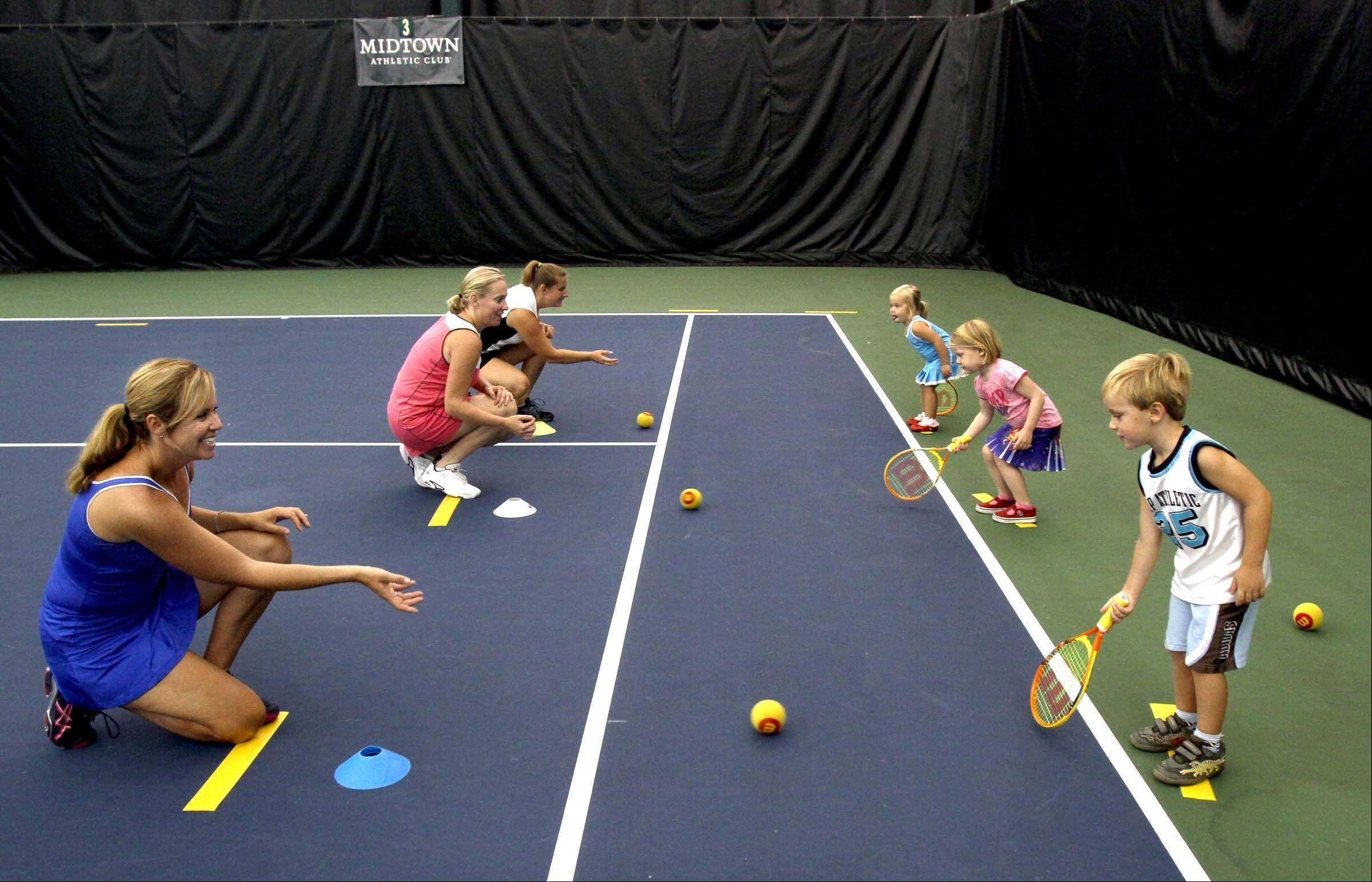 Moms and their children take part in Midtown Athletic Club's toddler tennis program, Tennis Explorers. In the foreground, Maggie Tepas of Barrington works with her 4-year-old son, Luke.