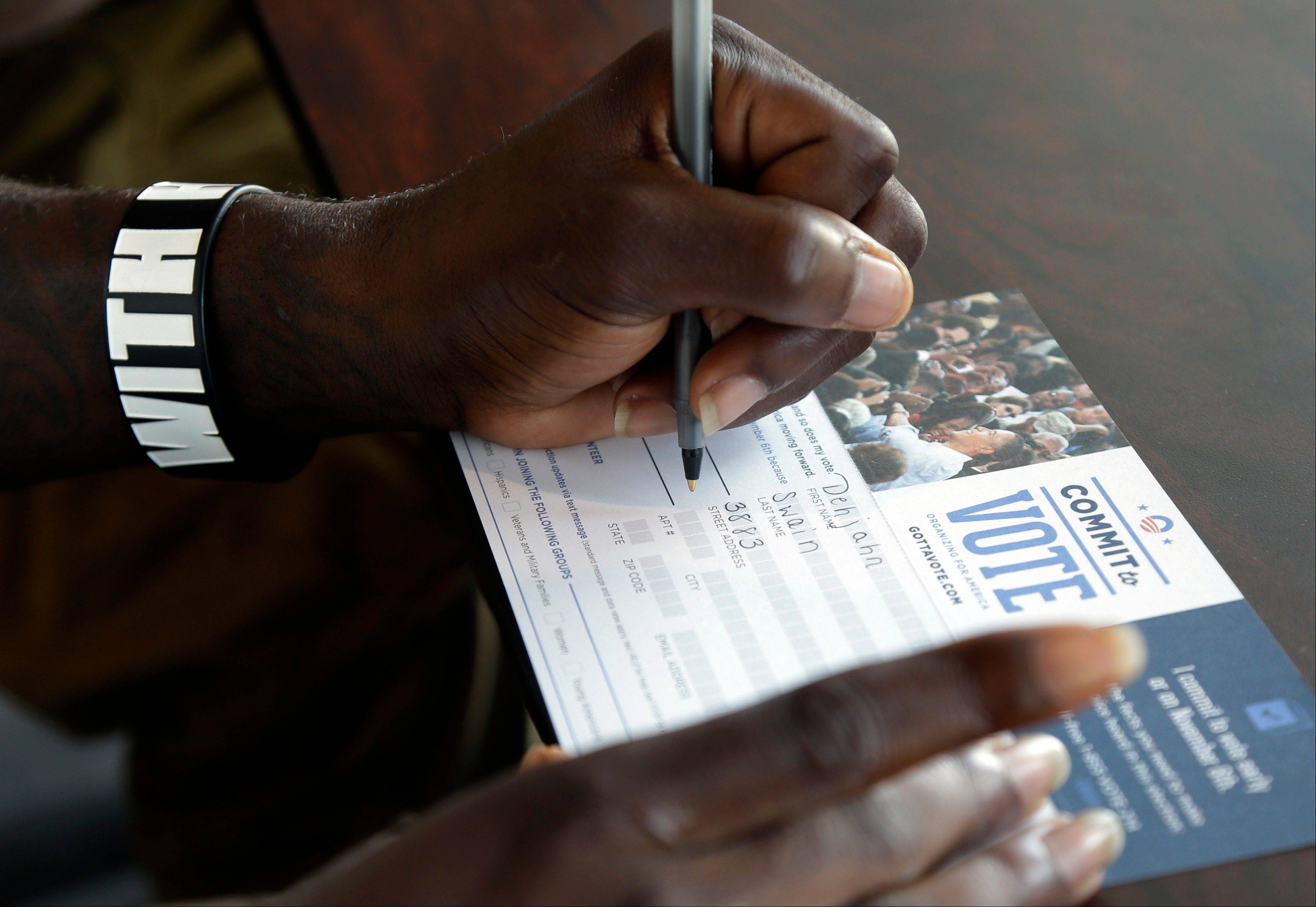 Dehjahn Swain, 19, fills out a Commit to Vote card after registering to vote at a campaign office for President Barack Obama, Monday, Oct. 8, 2012 in Miami. Tuesday is the last day to register to vote in the general election Nov. 6.