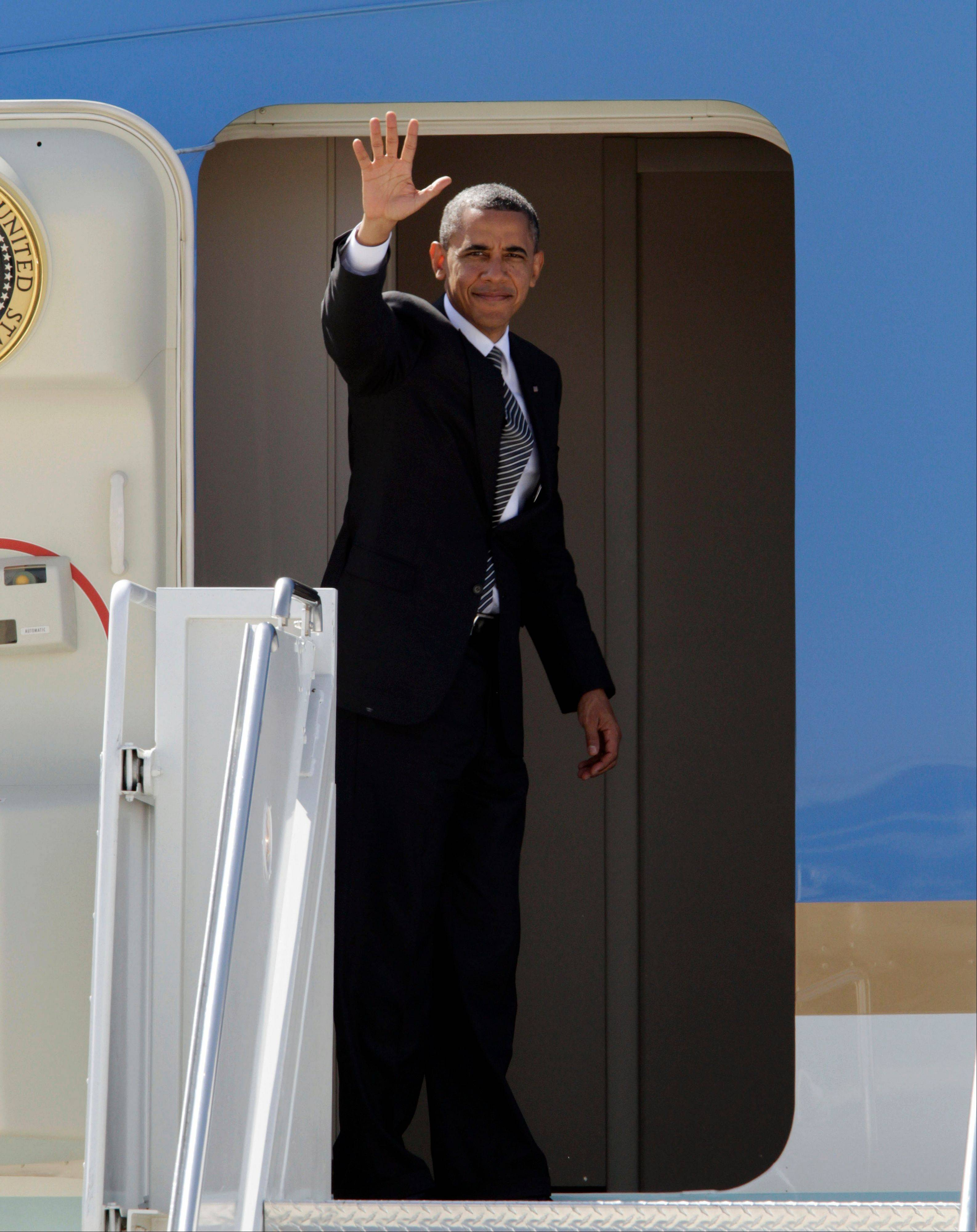 President Barack Obama waves from the door of Air Force One during his departure at the Meadows Field Airport in Bakersfield, Calif., Monday, Oct. 8, 2012.