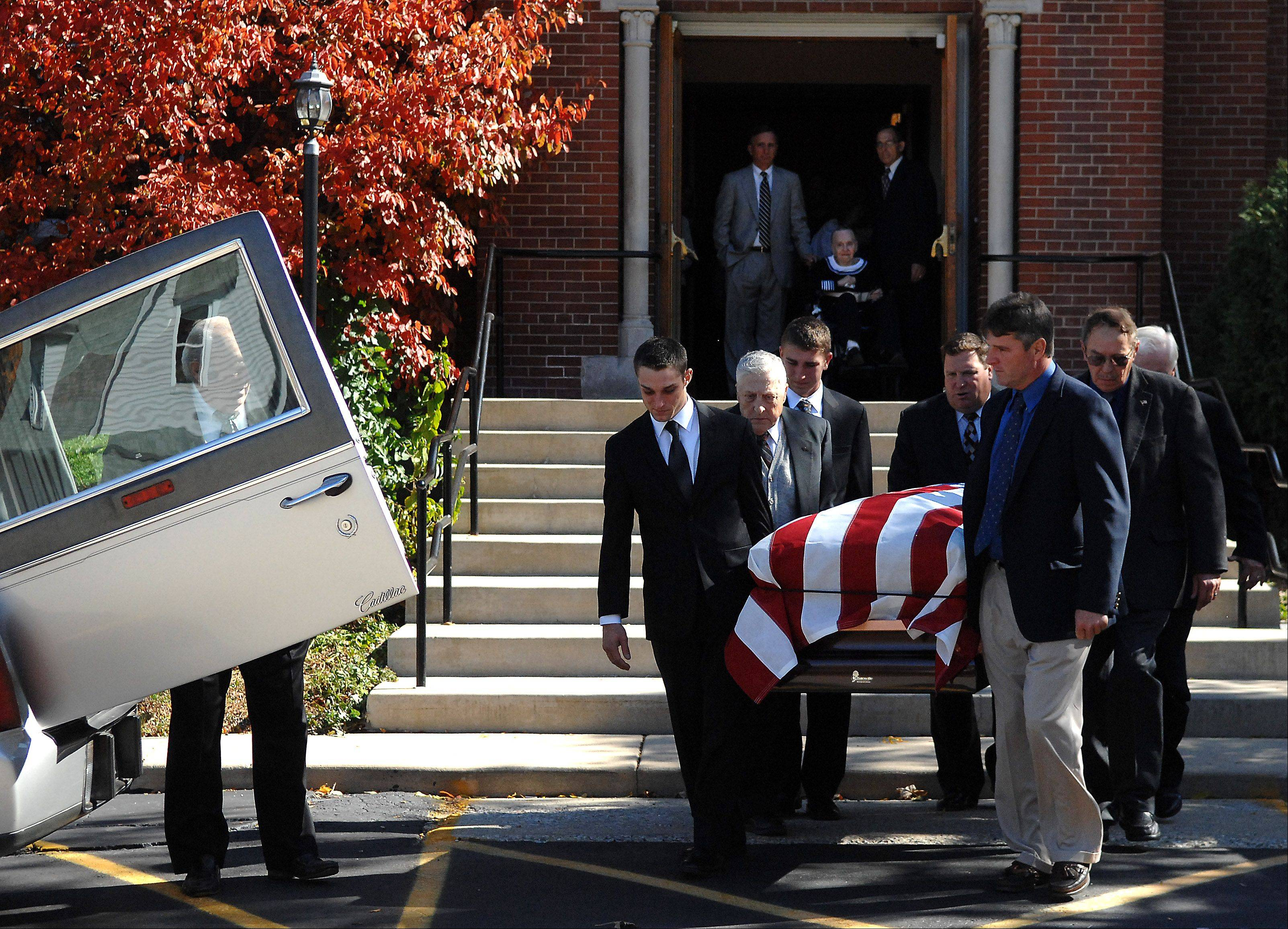 Theresa Kudlicki watches as pallbearers carry the casket of her husband, Robert, after a service Monday morning at St. Charles Borromeo Catholic Church in Hampshire. Besides his service to his community, he was in the Marines during the Korean War. He was buried with full military honors.