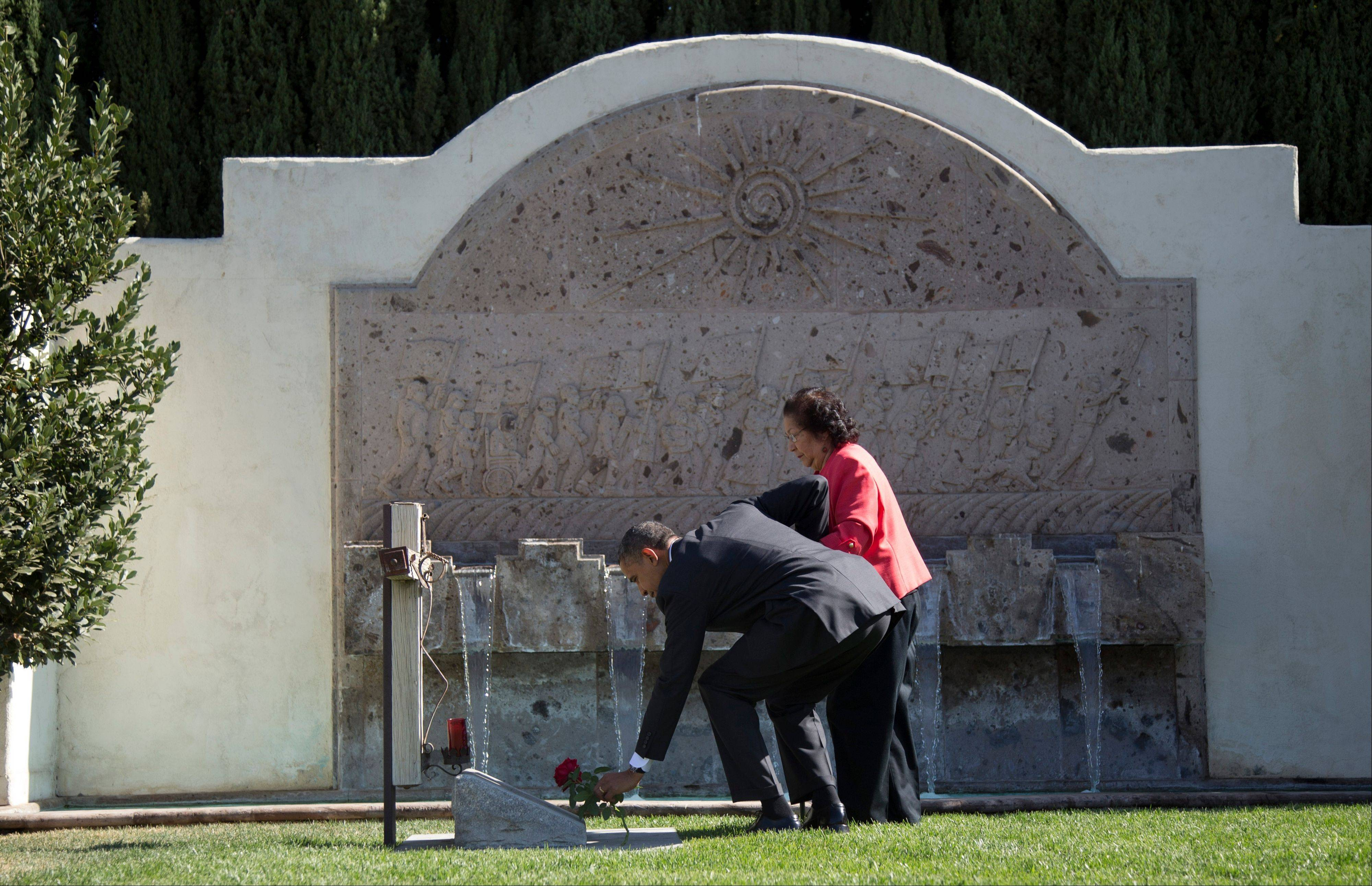 "President Barack Obama, accompanied by Cesar Chavez' widow, Helen F. Chavez, places a special ""Cesar Chavez"" red rose at the gravesite where Cesar E. Chavez was laid to rest in 1993, as he toured the Cesar E. Chavez National Monument Memorial Garden, Monday, Oct. 8, 2012, in Keene, Calif."
