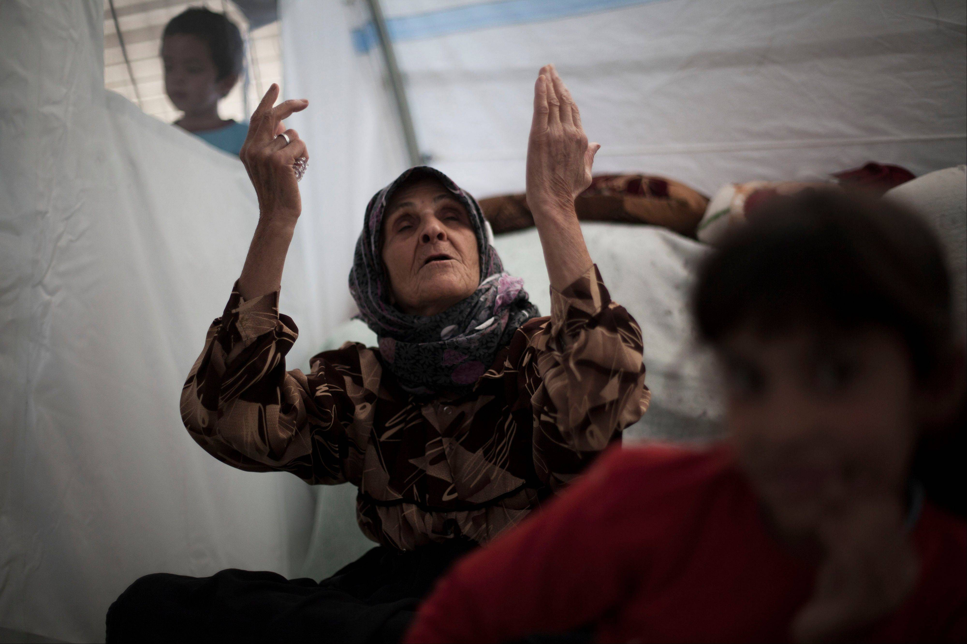 "An elderly Syrian woman, who fled her home with her family due to fighting between government forces and rebels, chants, ""Allah,"" meaning God in Arabic, inside her tent at a refugee camp near the Turkish border, in Azaz, Syria, Sunday."