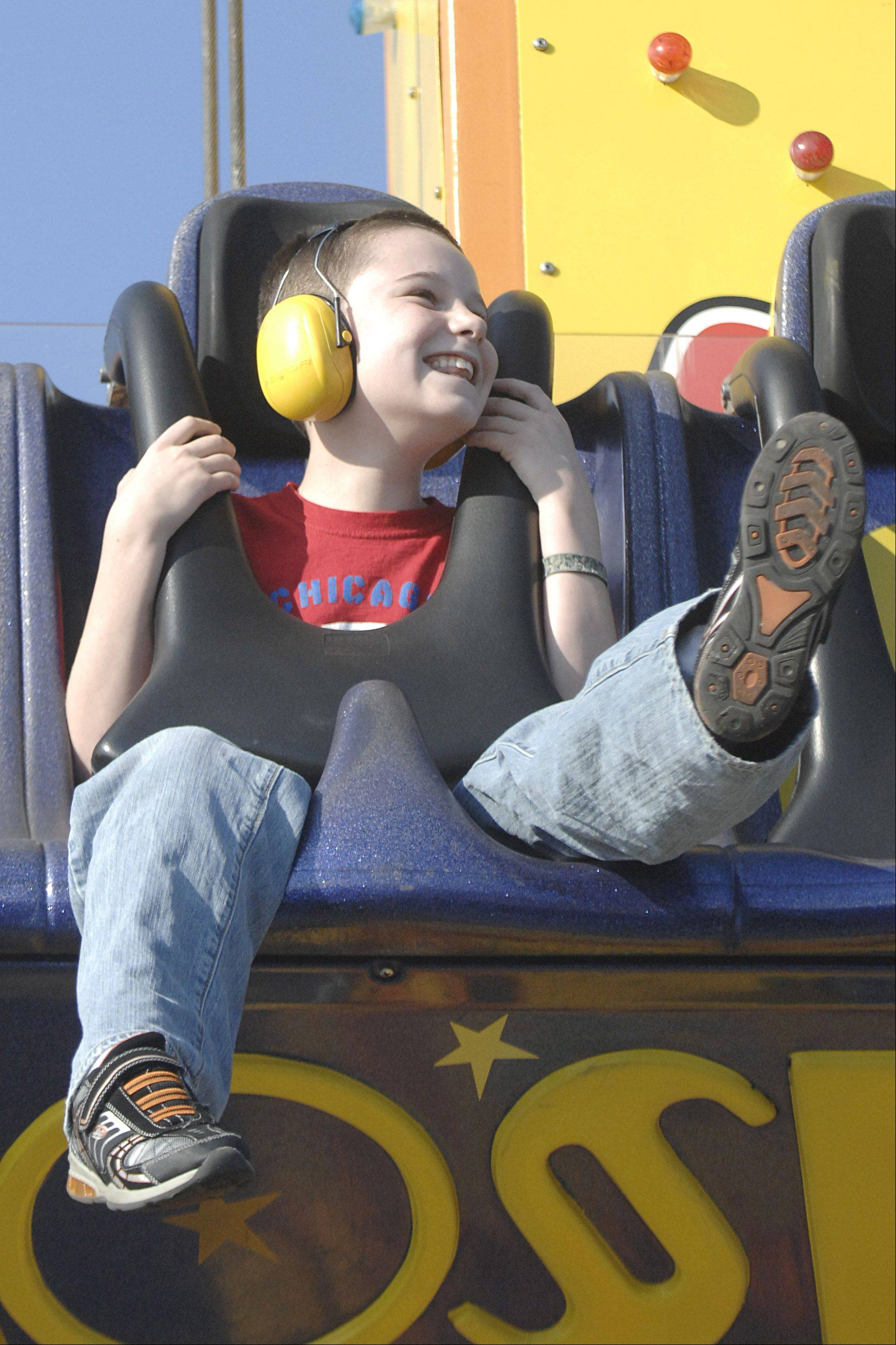Jason Kelly, 11, of Schaumburg kicks his heels in the air with excitement while in a downward plunge on the Freefall ride at the Huntley Fall Fest carnival on Friday, September 28. Jason's mom, Jill, says he's a fan of roller coasters, too. An hour was put aside for 15 families with special needs children who preregistered to have a chance to enjoy rides for free.