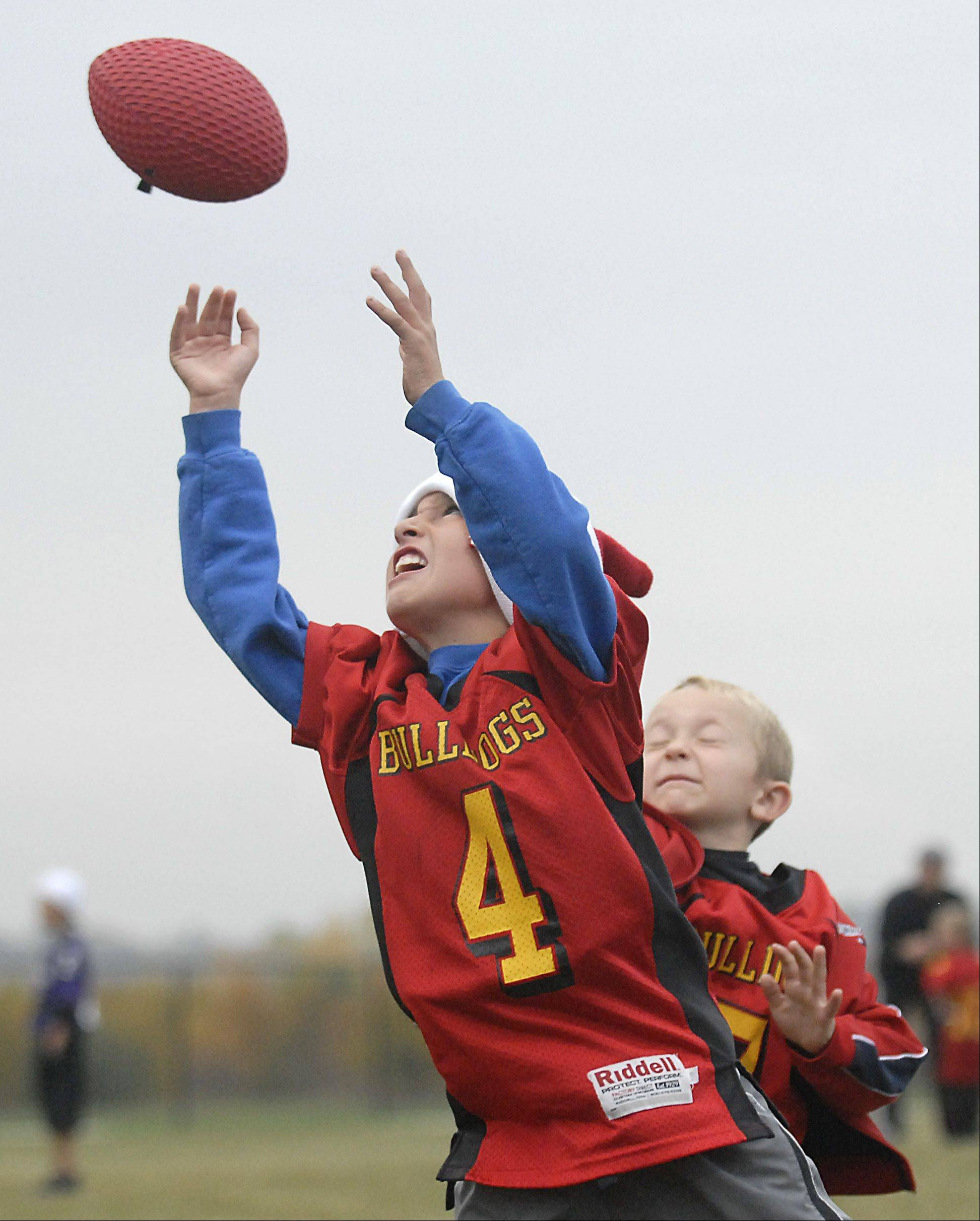 Alex Breytspraak , reaches up for a pass in front of Zach Sledz, both 7 and from Aurora, during a Batavia Youth Football league game at West Main Park in Batavia.