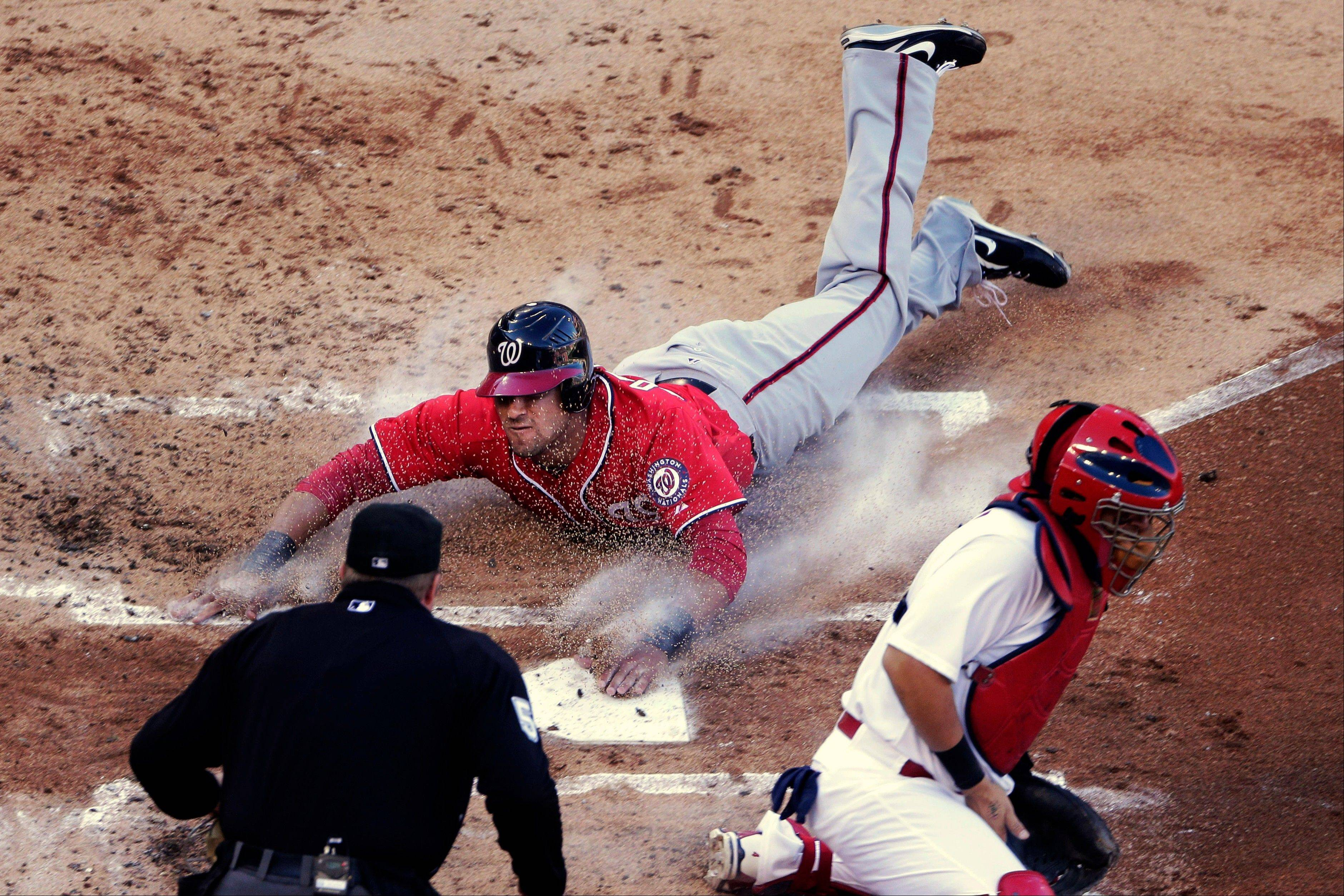 Washington Nationals' Ian Desmond, top, slides home past St. Louis Cardinals catcher Yadier Molina, bottom right, to score on a single by Jordan Zimmermann during the second inning of Game 2 of the National League division baseball series, Monday, Oct. 8, 2012, in St. Louis.