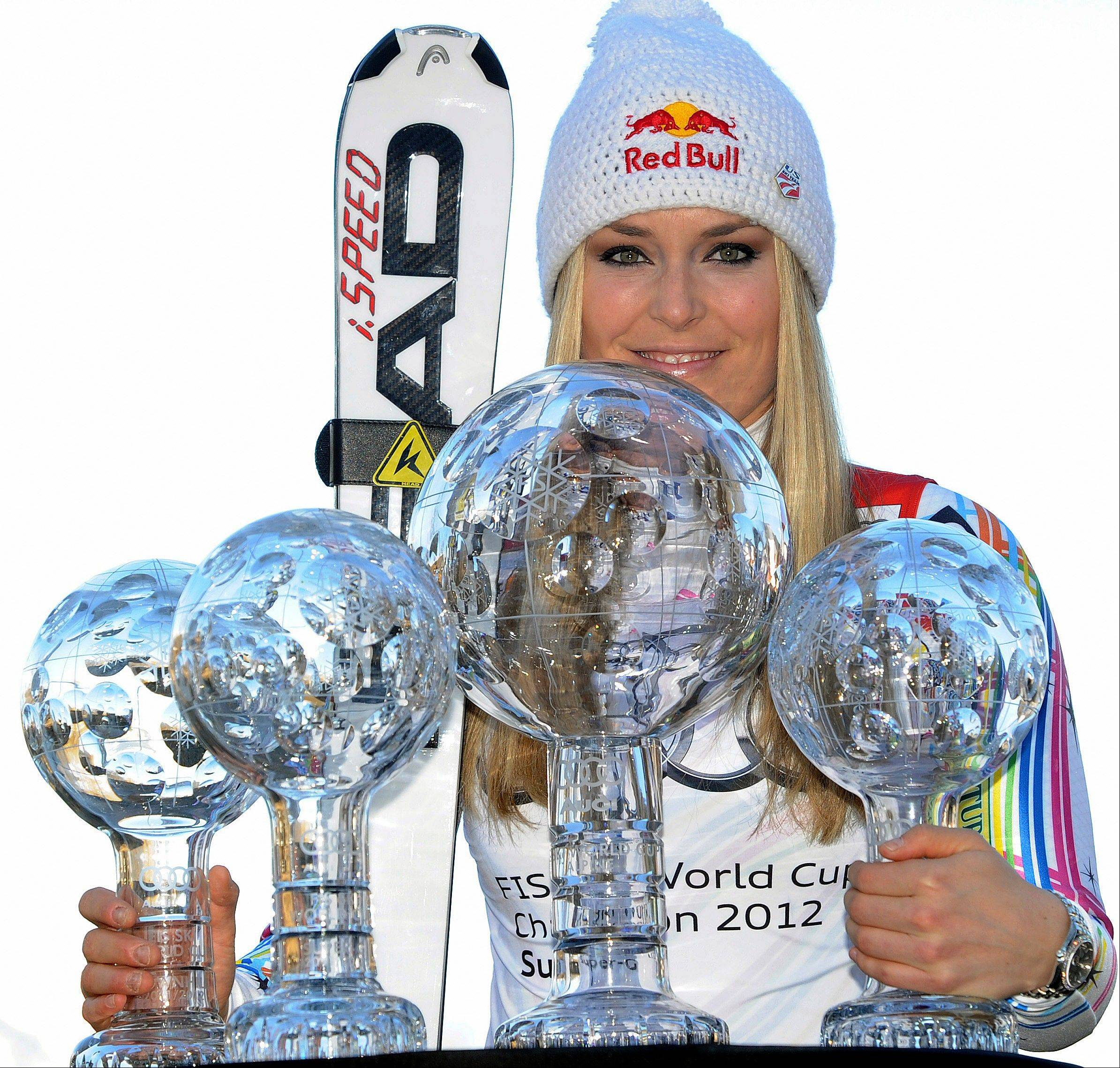 "This March 18, 2012 file photo shows Lindsey Vonn, of the United States, posing with her alpine ski, women's World Cup trophies for the super-G, super-combined, downhill and overall titles, in Schladming, Austria. The United States ski team says it hasn't had any ""formal discussion"" yet about the possibility of Lindsey Vonn entering a men's World Cup downhill next month. FIS secretary general Sarah Lewis tells The Associated Press the governing body can't make a decision on the matter until the team submits a formal request."