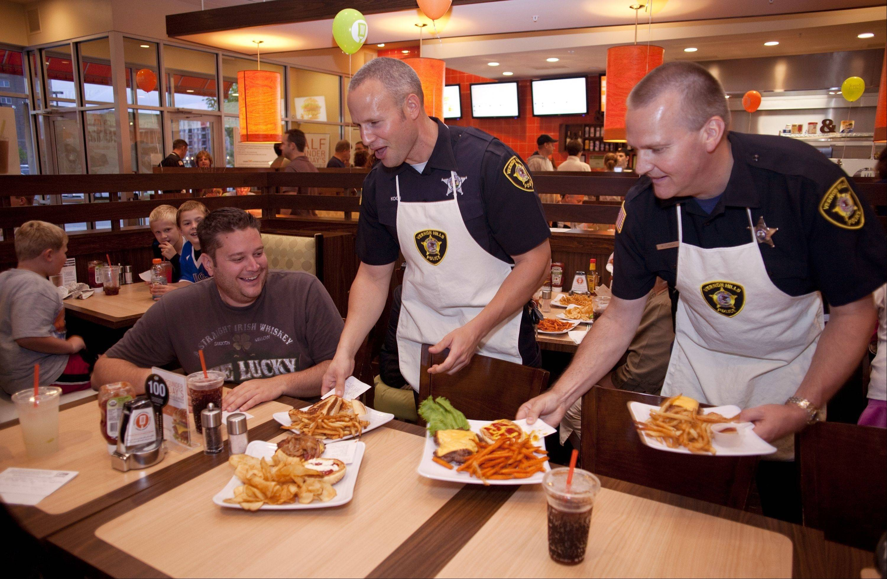 "Peter Lamberti, left gets a special delivery from Vernon Hills officers Jim Koch and Bob Lynch at Tom & Eddie's in Vernon Hills. Uniformed officers from the Vernon Hills Police Department served customers during a fundraiser for Special Olympics Illinois, ""Burgers & Badges."""