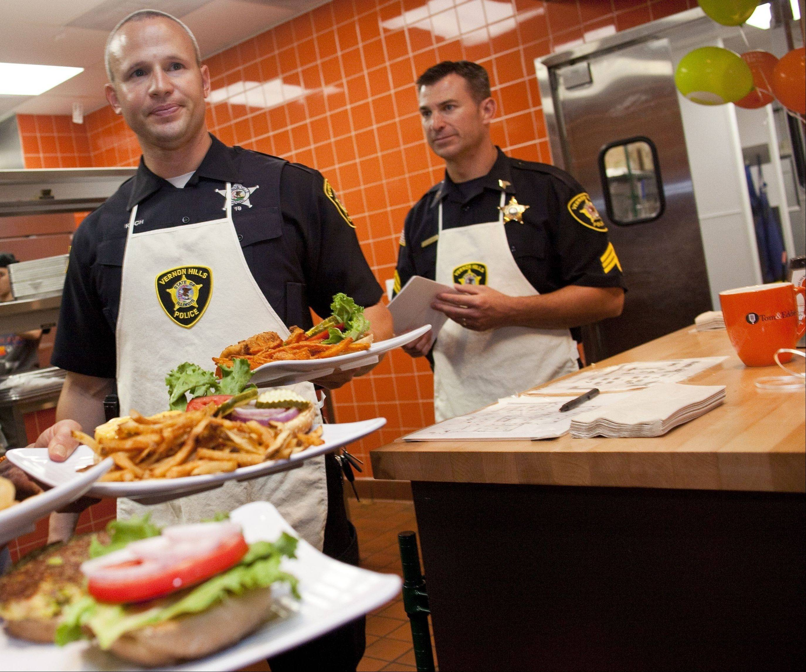 "Vernon Hills officer Jim Koch, and Sgt. Jim Levicki bring out an order of gourmet burgers during the ""Burgers & Badges"" fundraiser."