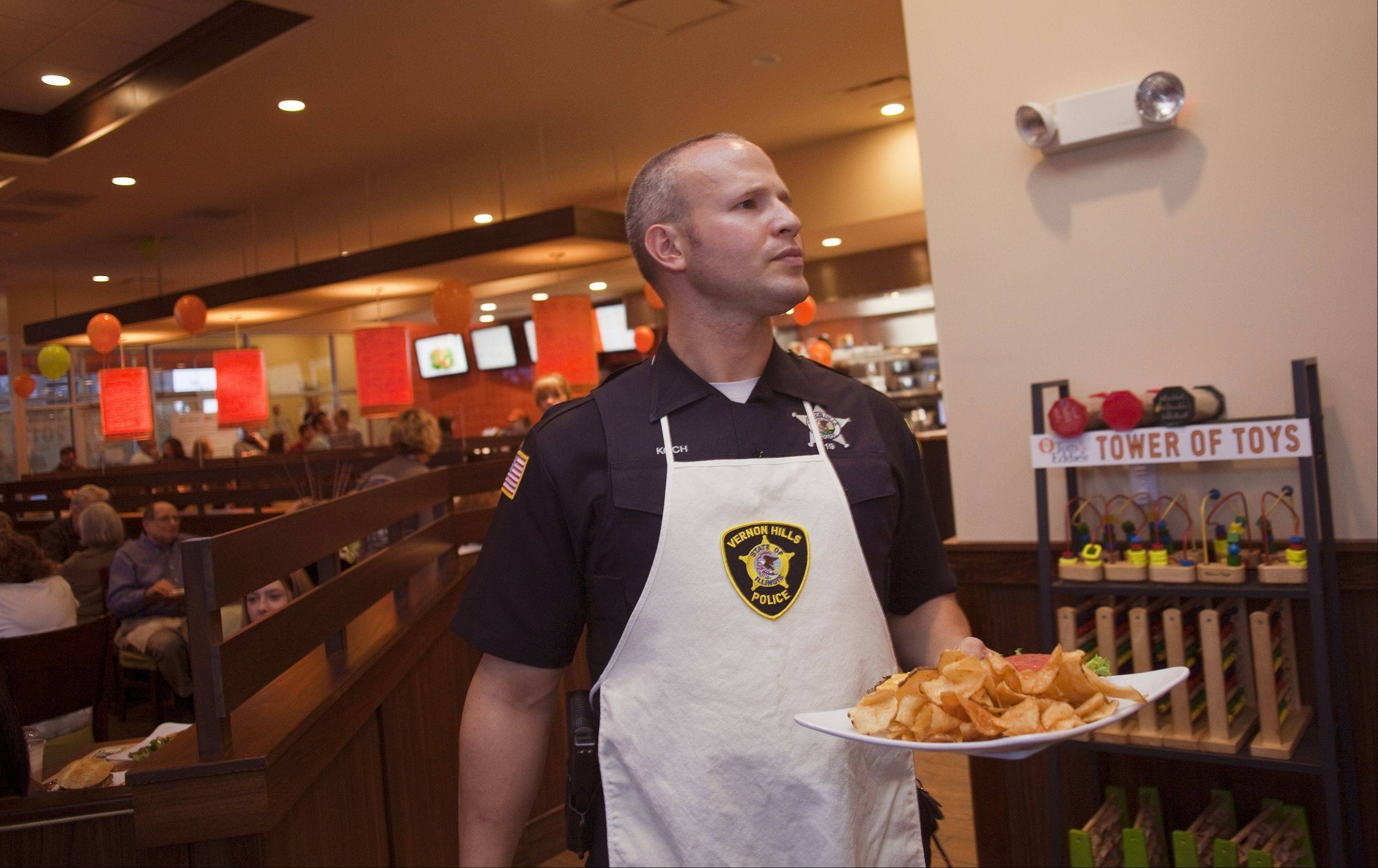 "Vernon Hills officer Jim Koch serves a plate of food during ""Burgers & Badges."""
