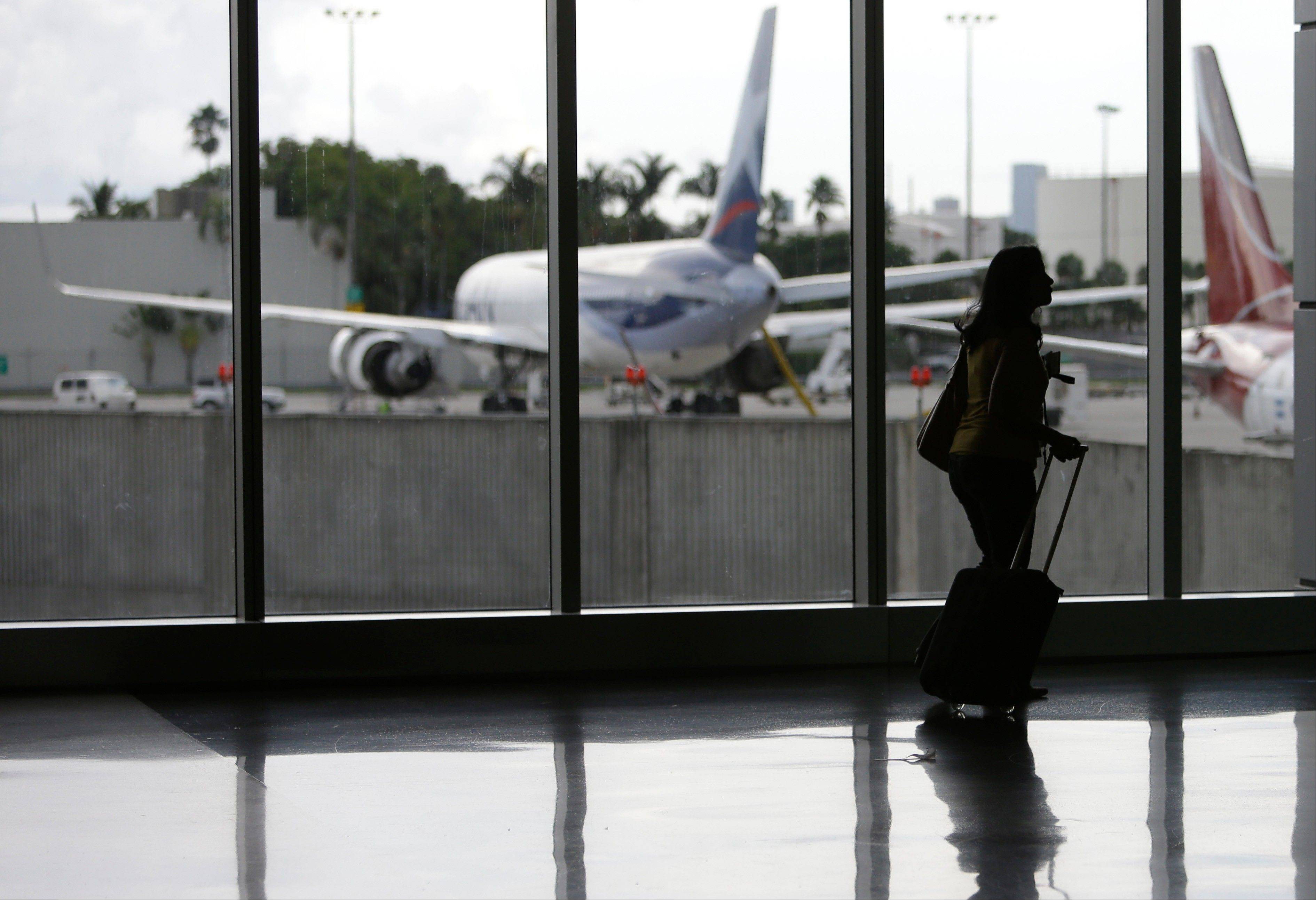 A passenger walks through the south terminal at Miami International Airport in Miami. U.S. companies are continuing to cut back on employee travel plans amid uncertainty surrounding the health of the economy. Americans are expected to take 438.1 million business trips this year, down 2 percent from last year, the Global Business Travel Association said Tuesday.