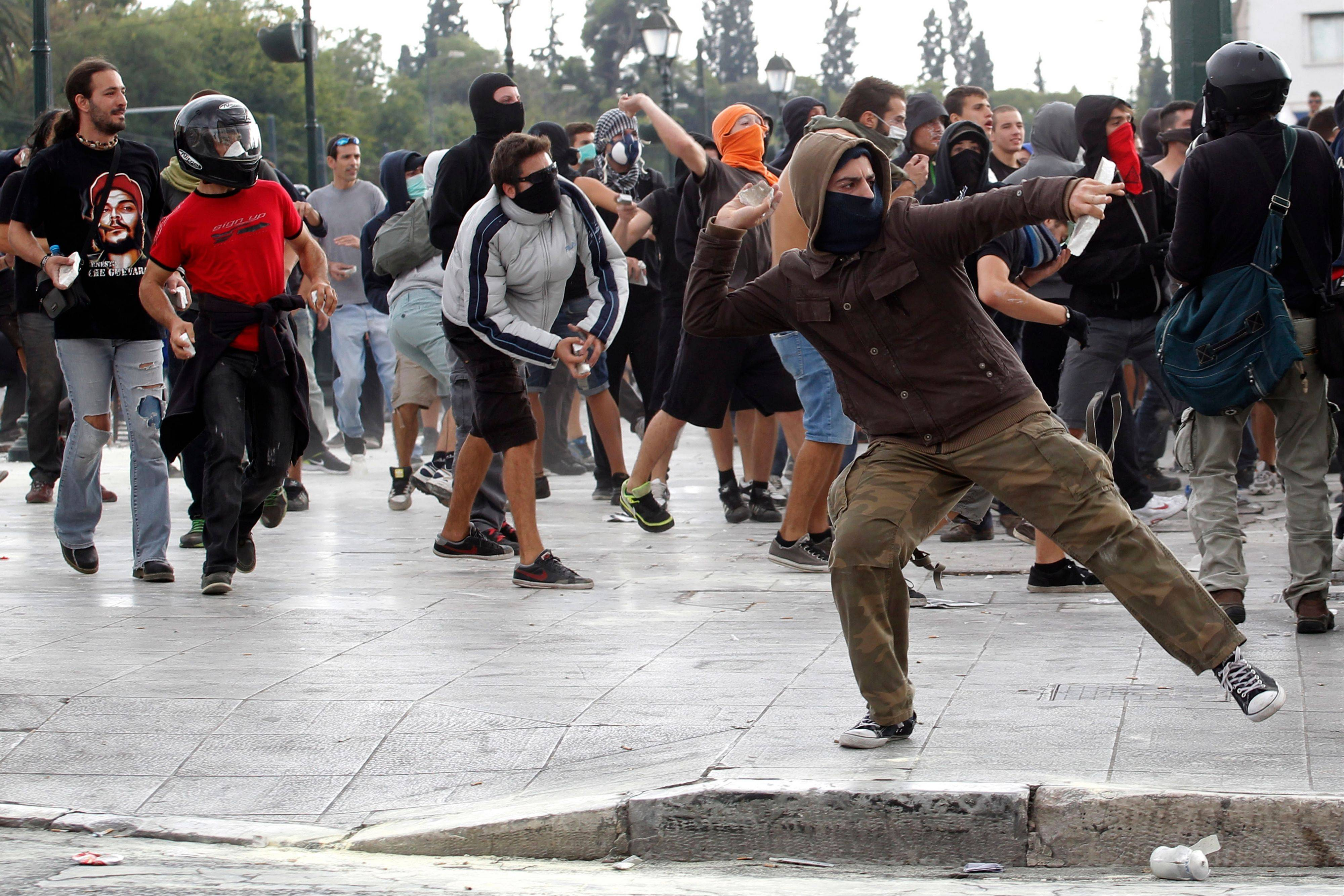Protesters throw stones to riot police Tuesday during clashes in central Athens. German Chancellor Angela Merkel got a hostile reception from ordinary Greeks Tuesday when she flew into Athens on her first visit to the country since its debt crisis erupted three years ago.