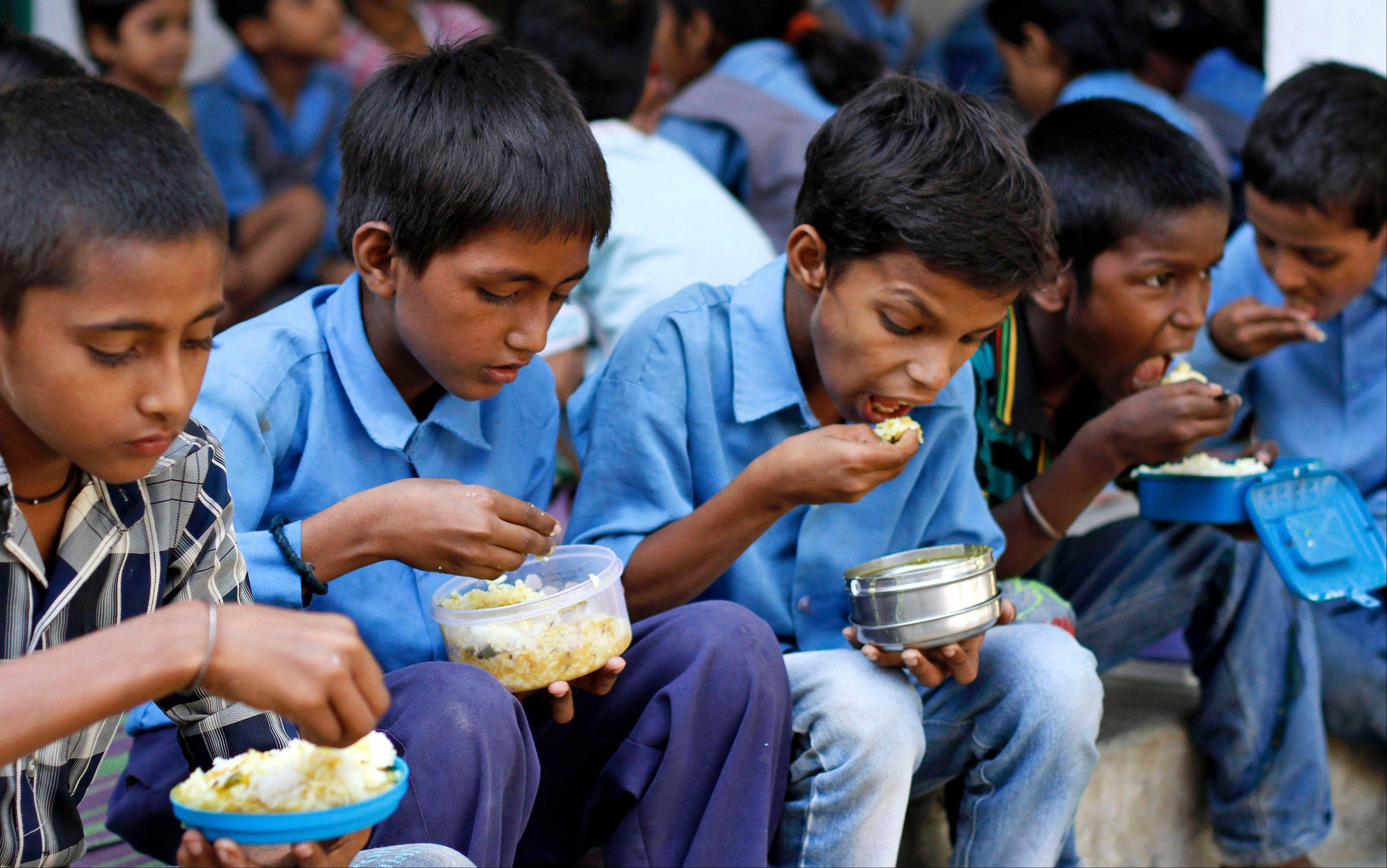 Indian schoolchildren eat a free mid-day meal at a government school in Allahabad, India.