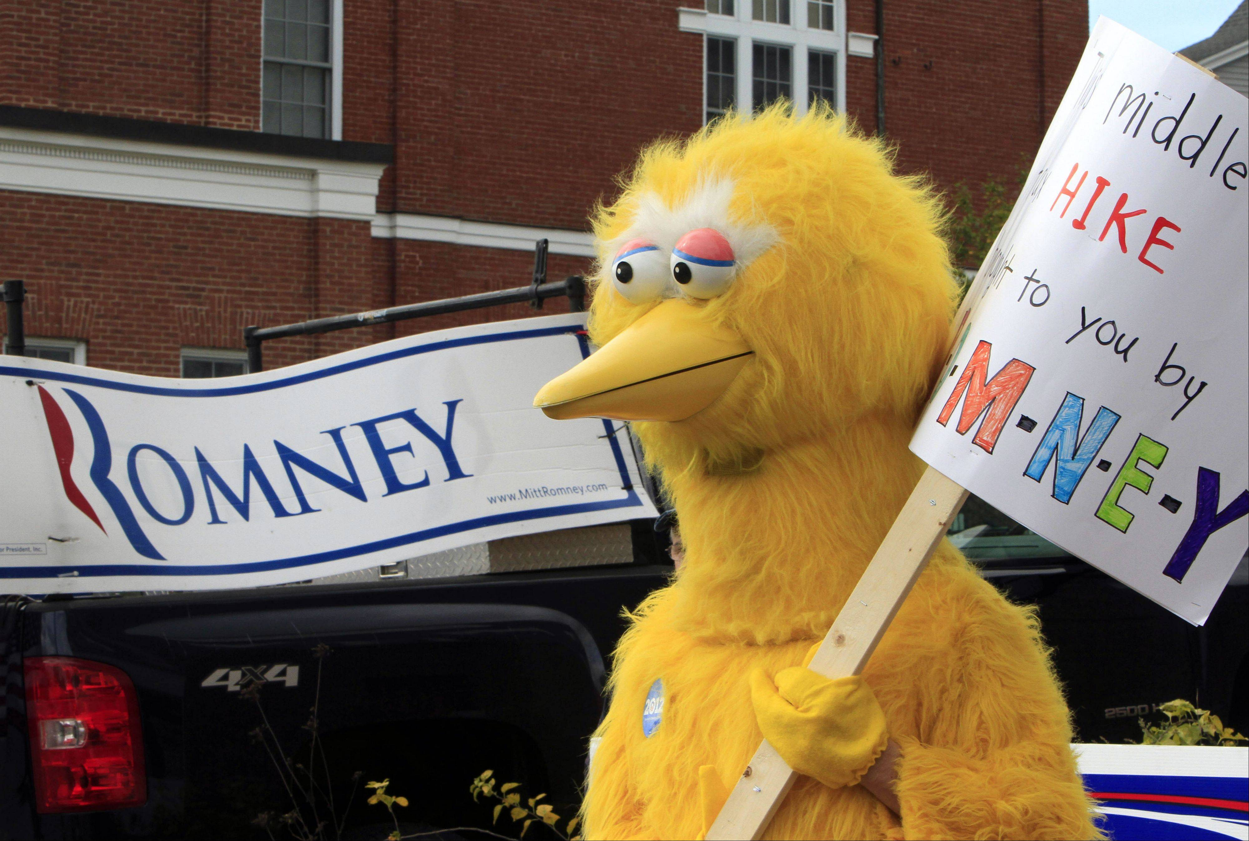 A person dressed as Big Bird holds a sign Monday outside Republican presidential candidate and former Massachusetts Gov. Mitt Romney�s headquarters in Derry, N.H. where House Speaker John Boehner of Ohio was about to speak to supporters.