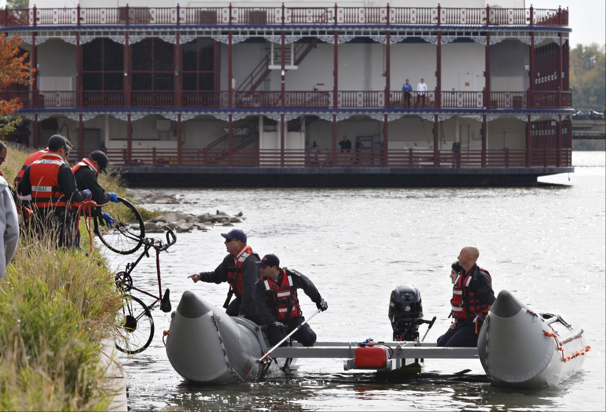 Elgin and South Elgin Fire Department personnel pull a bike from the Fox River as they continue to look for a body discovered there earlier by a fisherman.