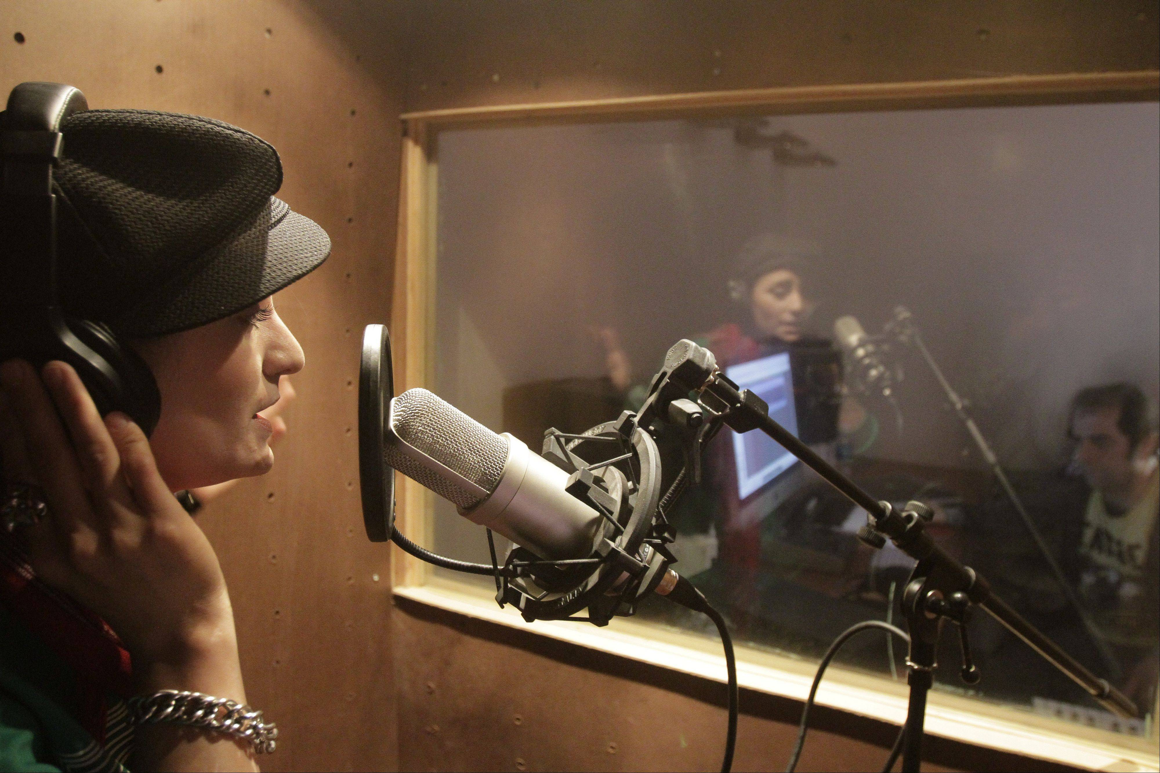 In this Wednesday, Oct. 3, 2012 photo, Afghanistan's first female rapper Sosan Firooz sings in a studio in Kabul, Afghanistan. Firooz, 23-year-old singer is making history in her homeland where society frowns on women who take the stage.