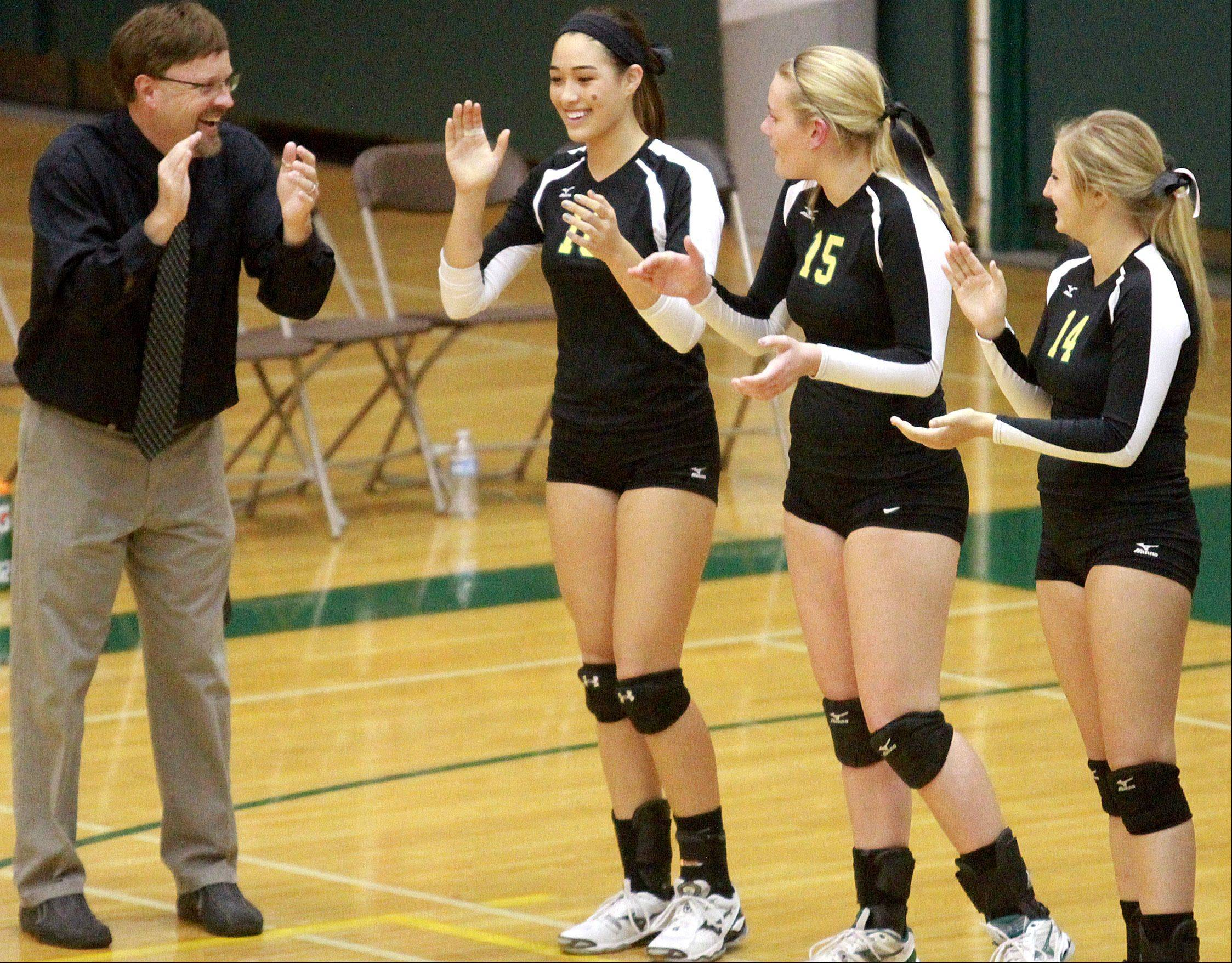Fremd coach Curt Pinley, left, greets his Vikings during player introductions before Tuesday�s contest against visiting Palatine. Fremd won to get Pinley his 300th girls volleyball coaching victory.