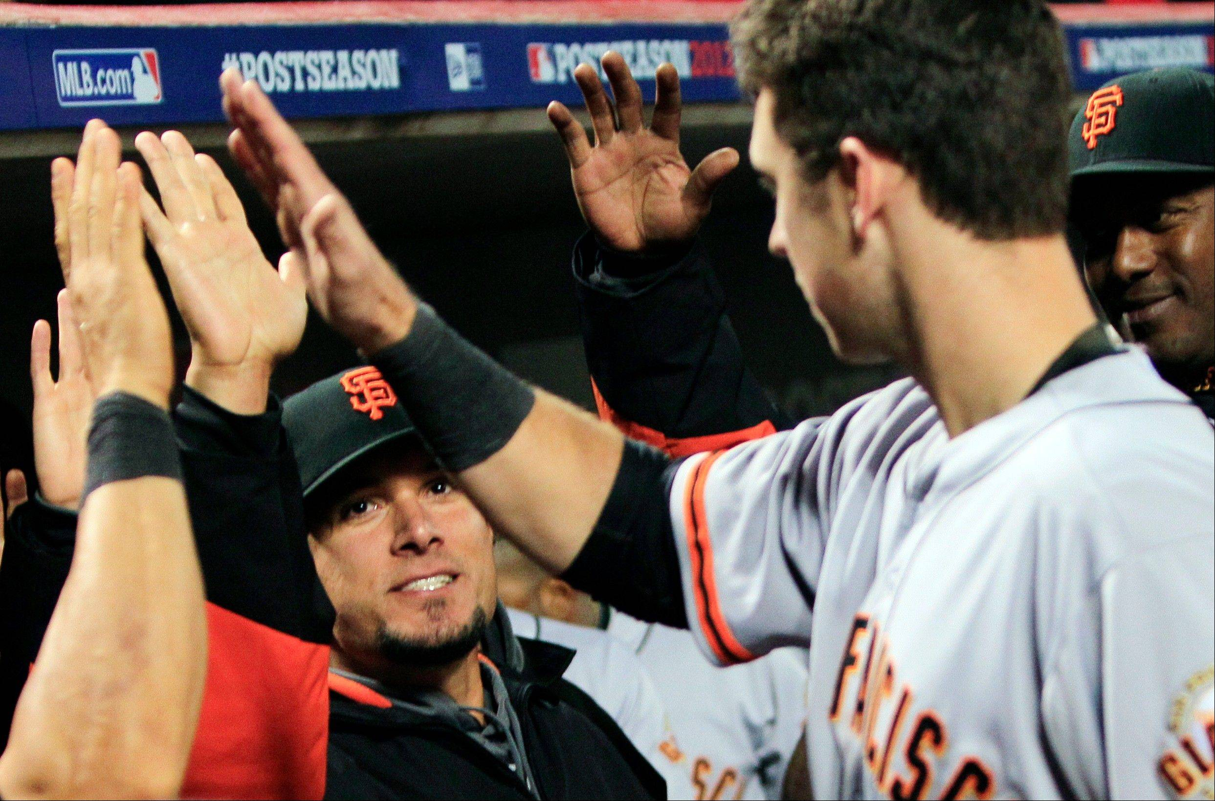 San Francisco Giants catcher Buster Posey, right, is congratulated after scoring in the 10th inning Tuesday during Game 3 of the National League division baseball series against the Cincinnati Reds in Cincinnati. The Giants won 2-1 in the 10th inning to cut their playoff deficit to 2-1.