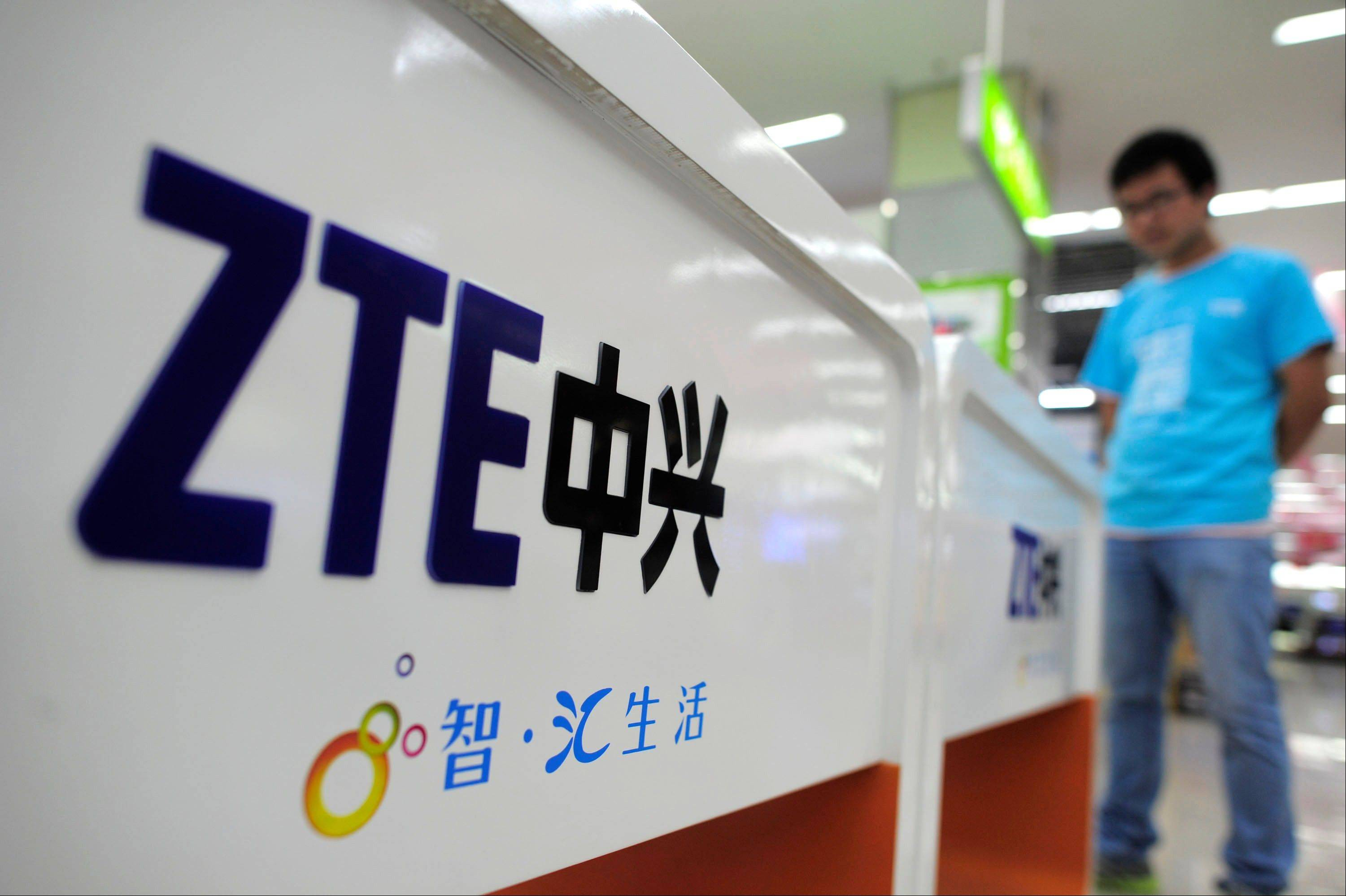 Asalesperson stands at counters selling mobile phones produced by ZTE Corp. at an appliance store in Wuhan, in central China's Hubei province.
