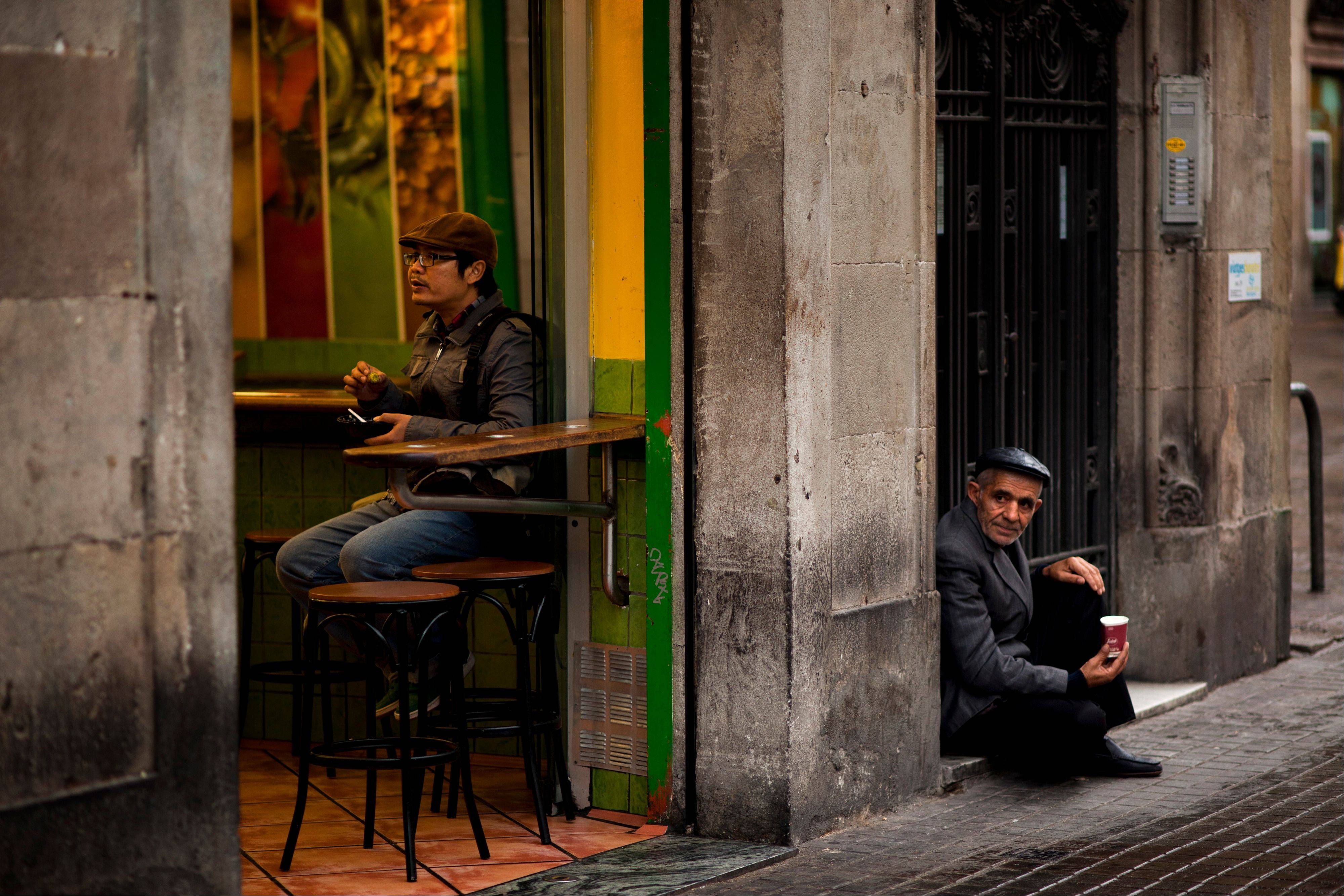 Atourist eats inside a restaurant as a man begs in the street in Barcelona, Spain. Spain�s Red Cross is launching its first-ever public appeal for donations to help the growing number Spaniards in need of help because of the economic crisis.