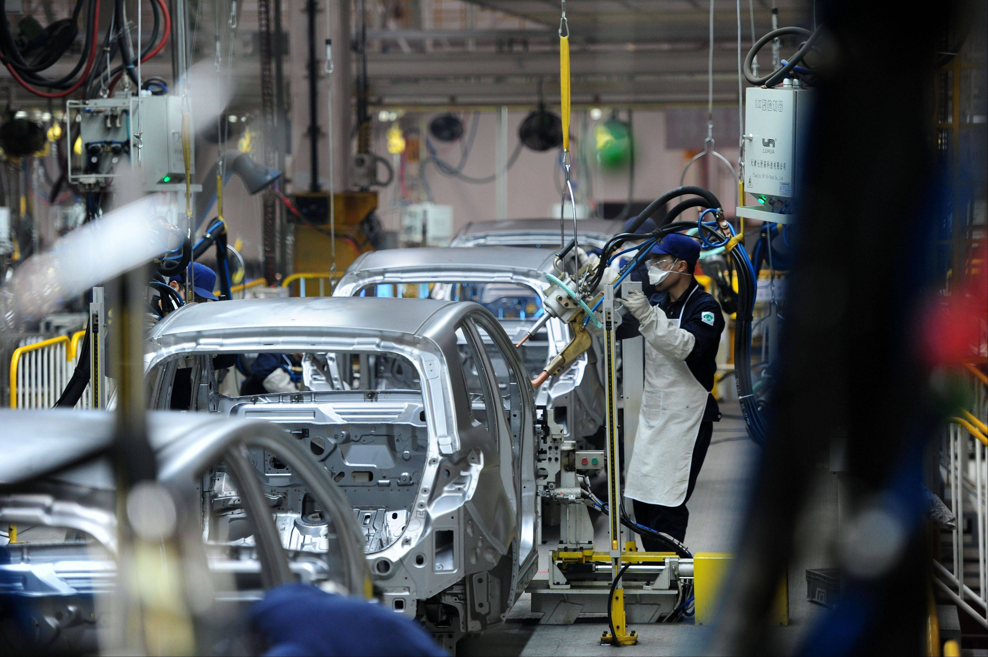 Workers assemble cars at the factory of BAIC Motor Corporation in Zhuzhou in south China's Hunan province. Plagued by uncertainty and fresh setbacks, the world economy has weakened further and will grow more slowly over the next year, the International Monetary Fund says in its latest forecast.
