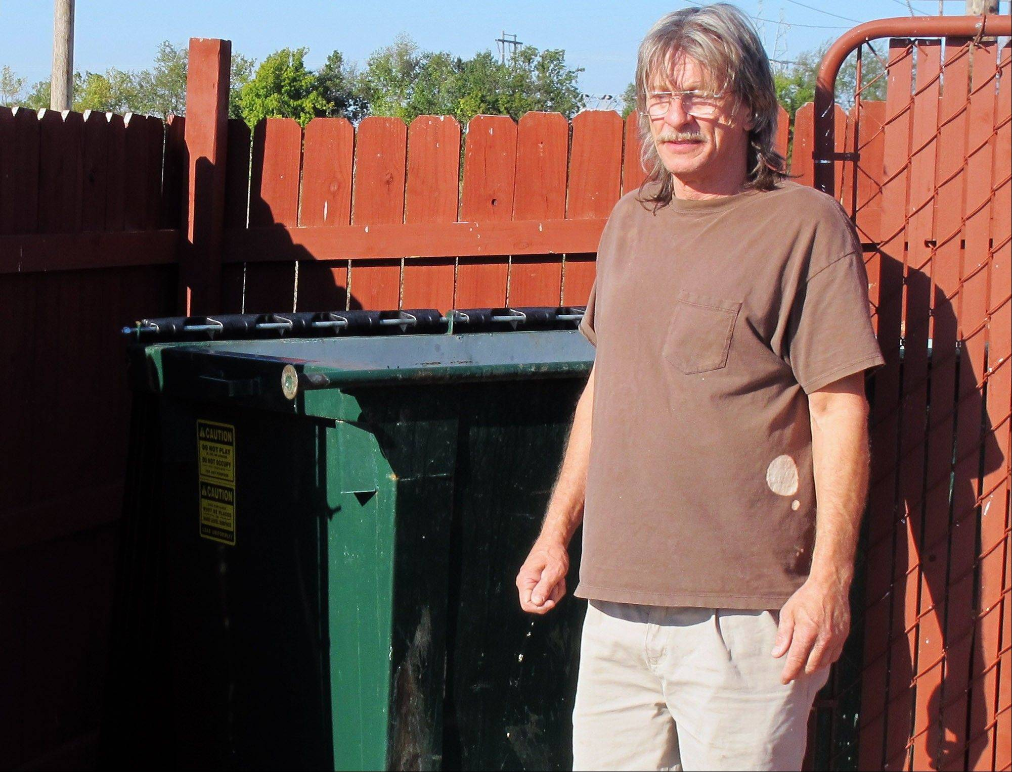 Ralph Smith, a maintenance worker at the Legacy Inn & Suites, stands in front of the trash bin where he found discarded bomb-making materials on Tuesday, Oct. 9, 2012, in Miami, Okla. Smith reported the find to authorities last week, and they later arrested Gregory Arthur Weiler II for possession of an explosive device.