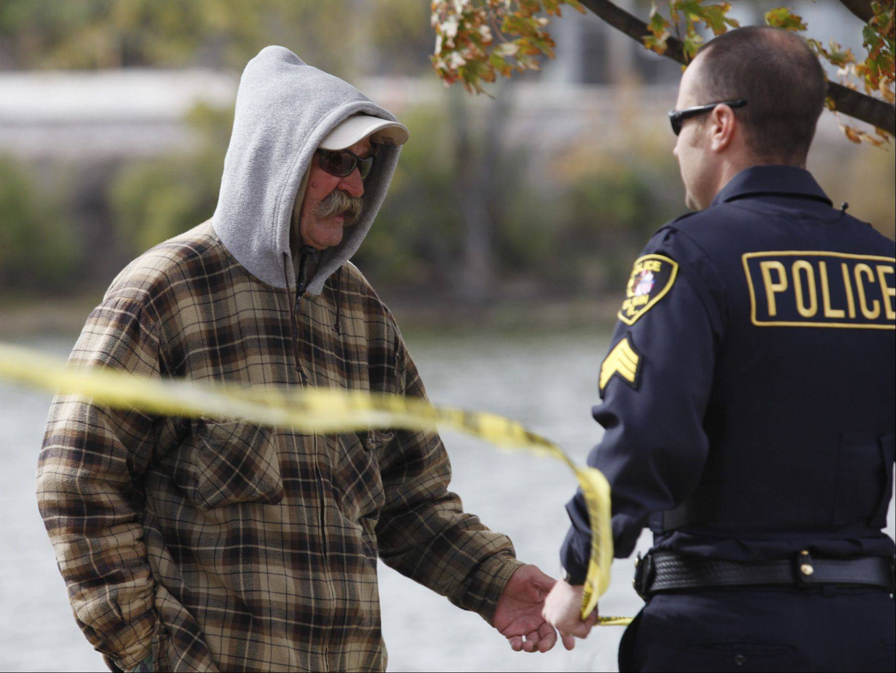 An Elgin police officer speaks with the fisherman who discovered a body Tuesday morning in the Fox River along Festival Park in downtown Elgin.