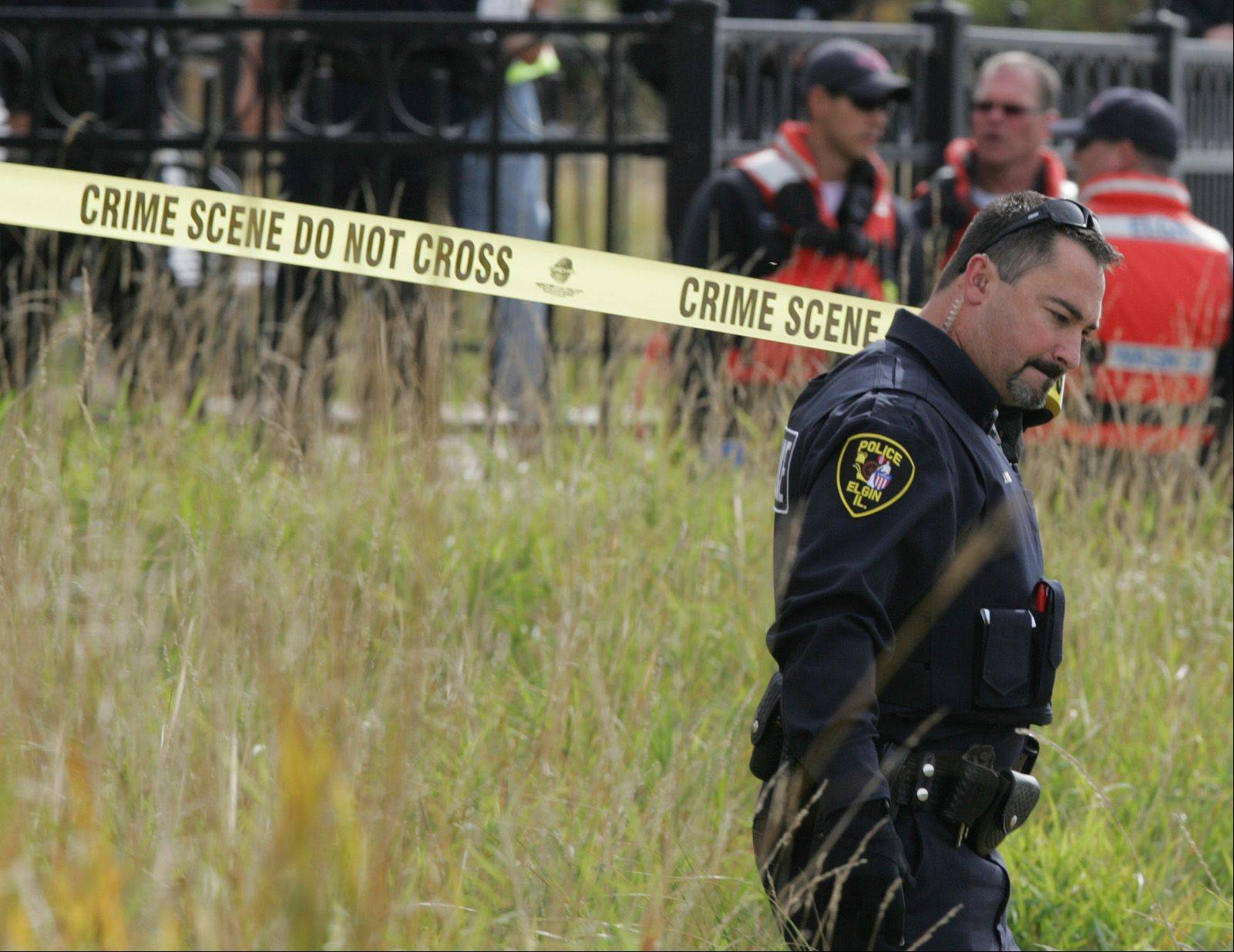 An Elgin police officer ropes off the area with crime scene tape as fire department personnel continue to attempt to find a body that a fisherman claimed to have found in the Fox River near Festival Park Tuesday morning.