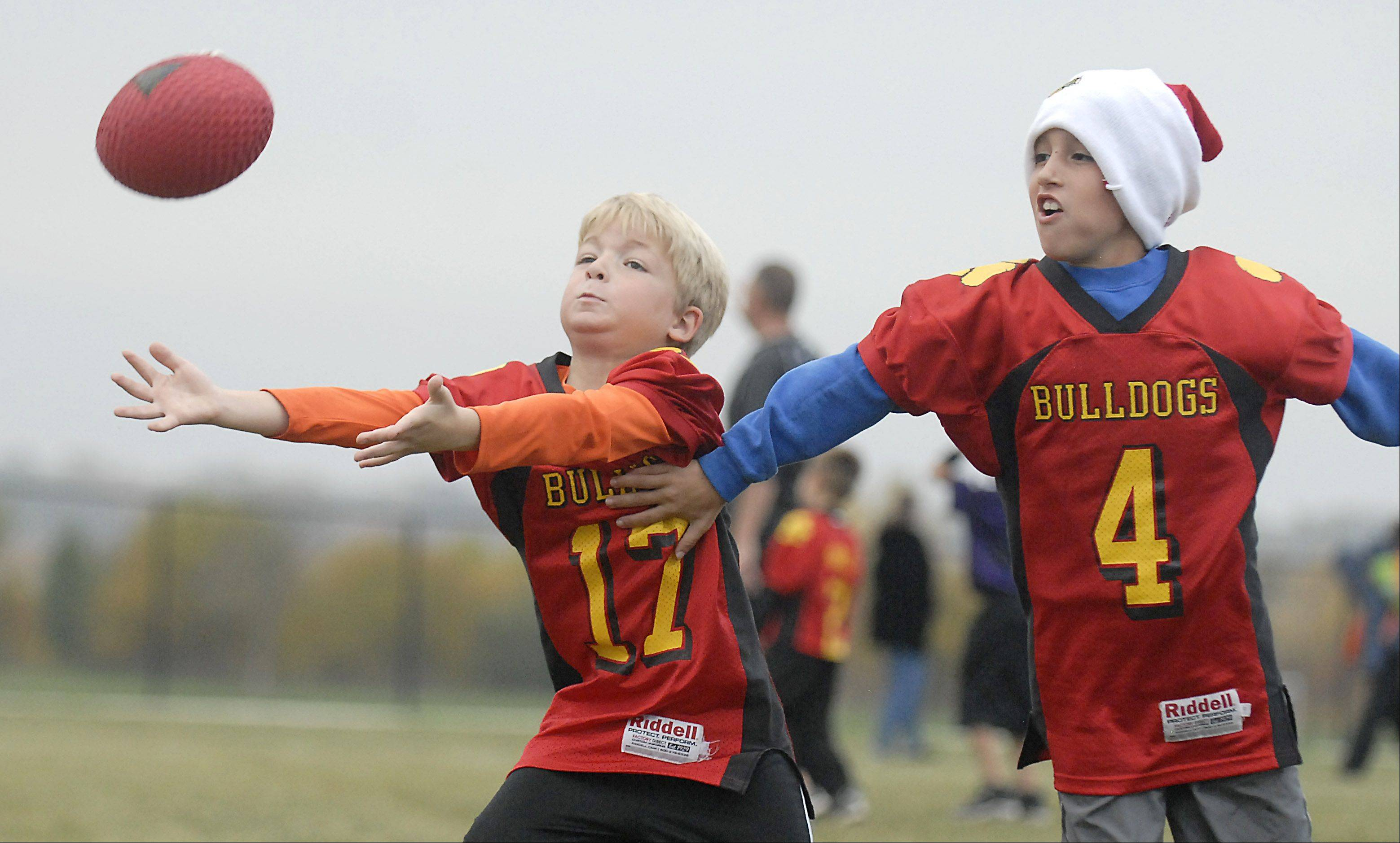 Cody Heeringa, 6, of Batavia, reaches out to receive a pass near Alex Breytspraak, 7, of Aurora during a Batavia Youth Football league in Batavia.