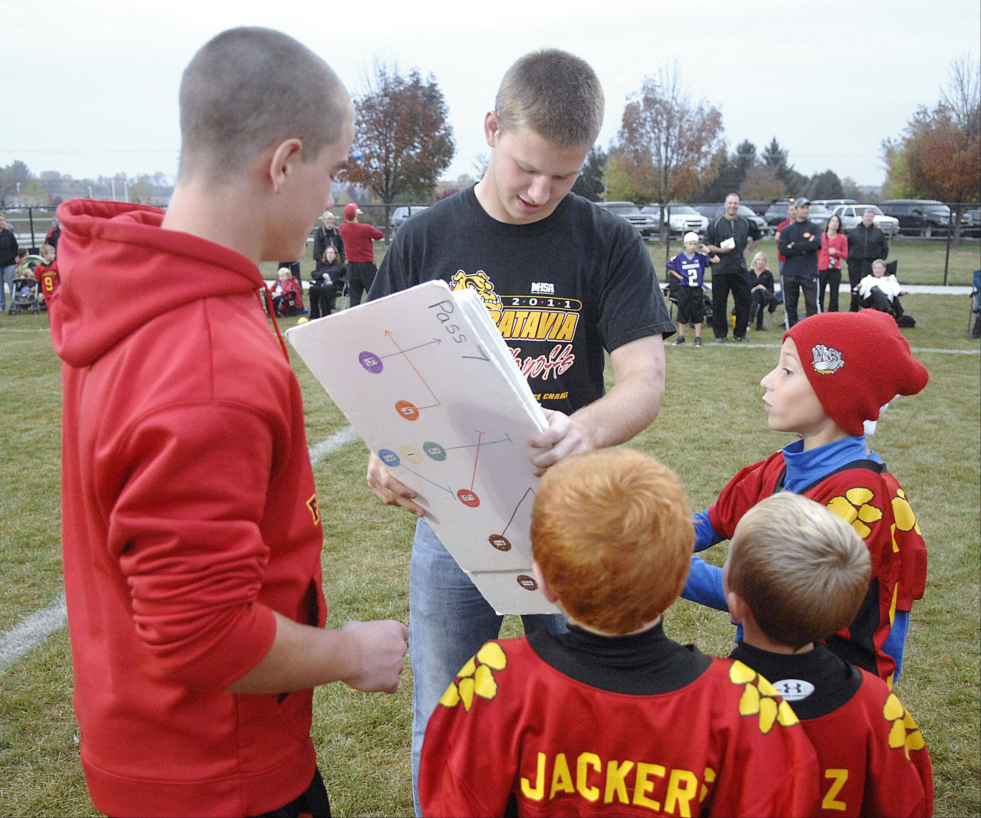 Batavia Youth Football league coaches and Batavia High School varsity football players Forrest Gilbertson, left, and Kevin Green, both 16, show their team the next play in their game.