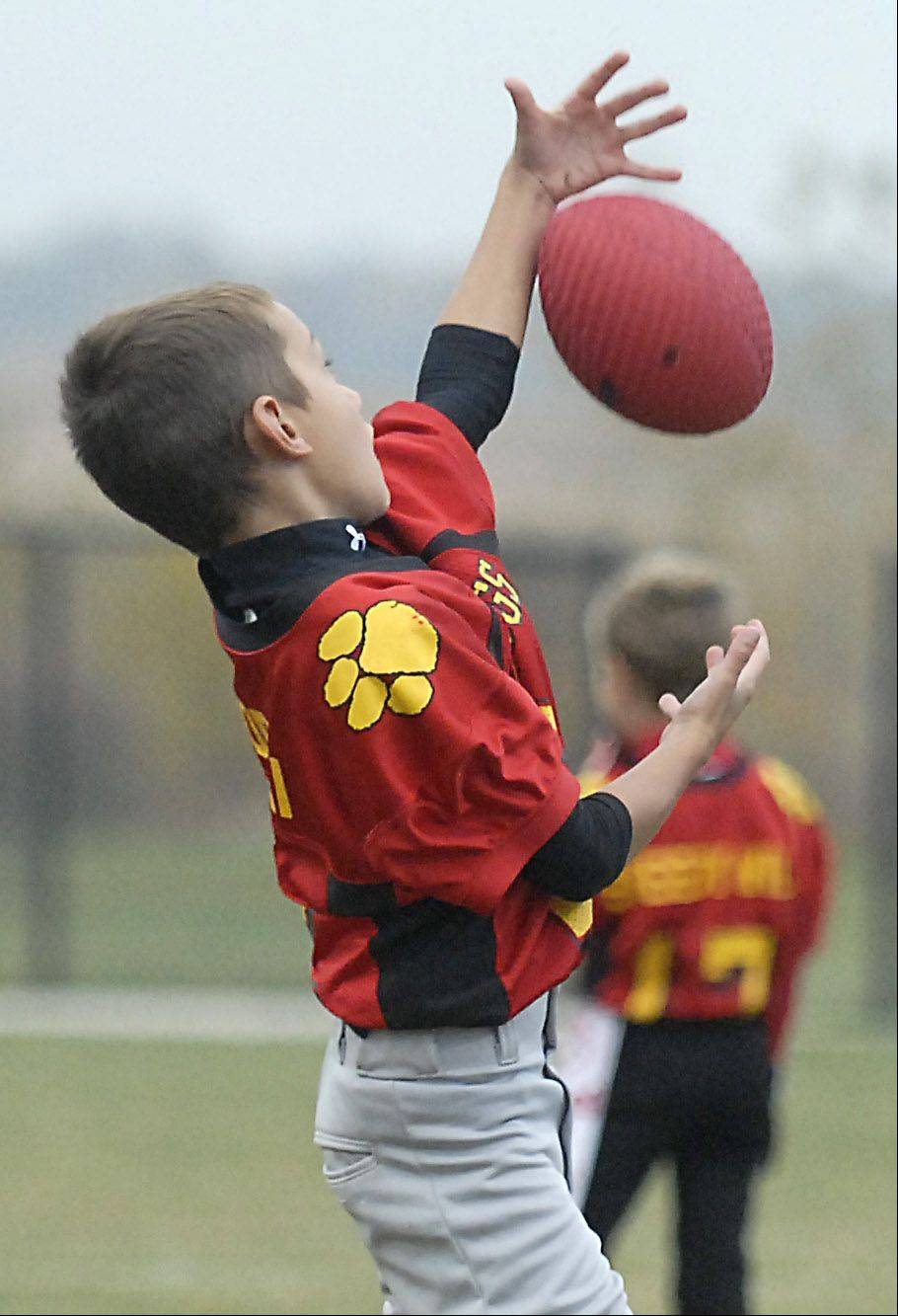 Andrew Gorski, 7, of Batavia reaches out for a pass during warm-ups before a game with the Batavia Youth Football league.