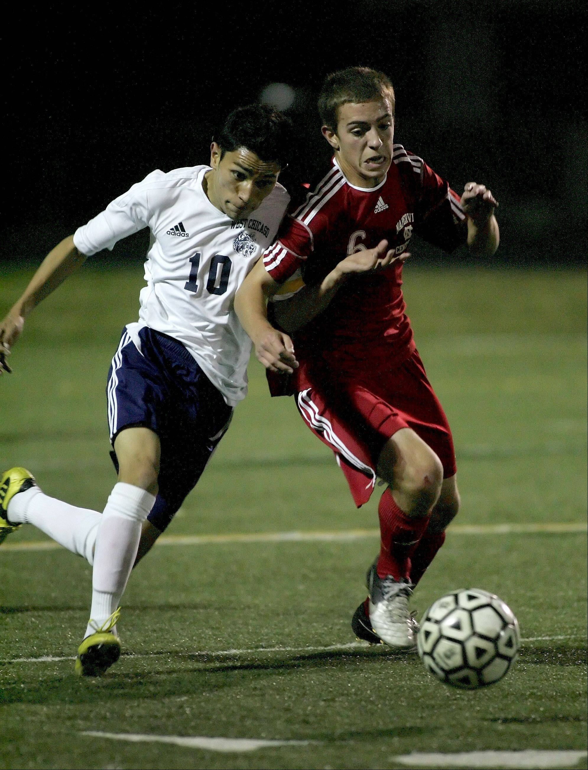 Diego Munoz of West Chicago, left and Mike West, righ, of Naperville Central fight for control of the ball in boys soccer action on Tuesday.