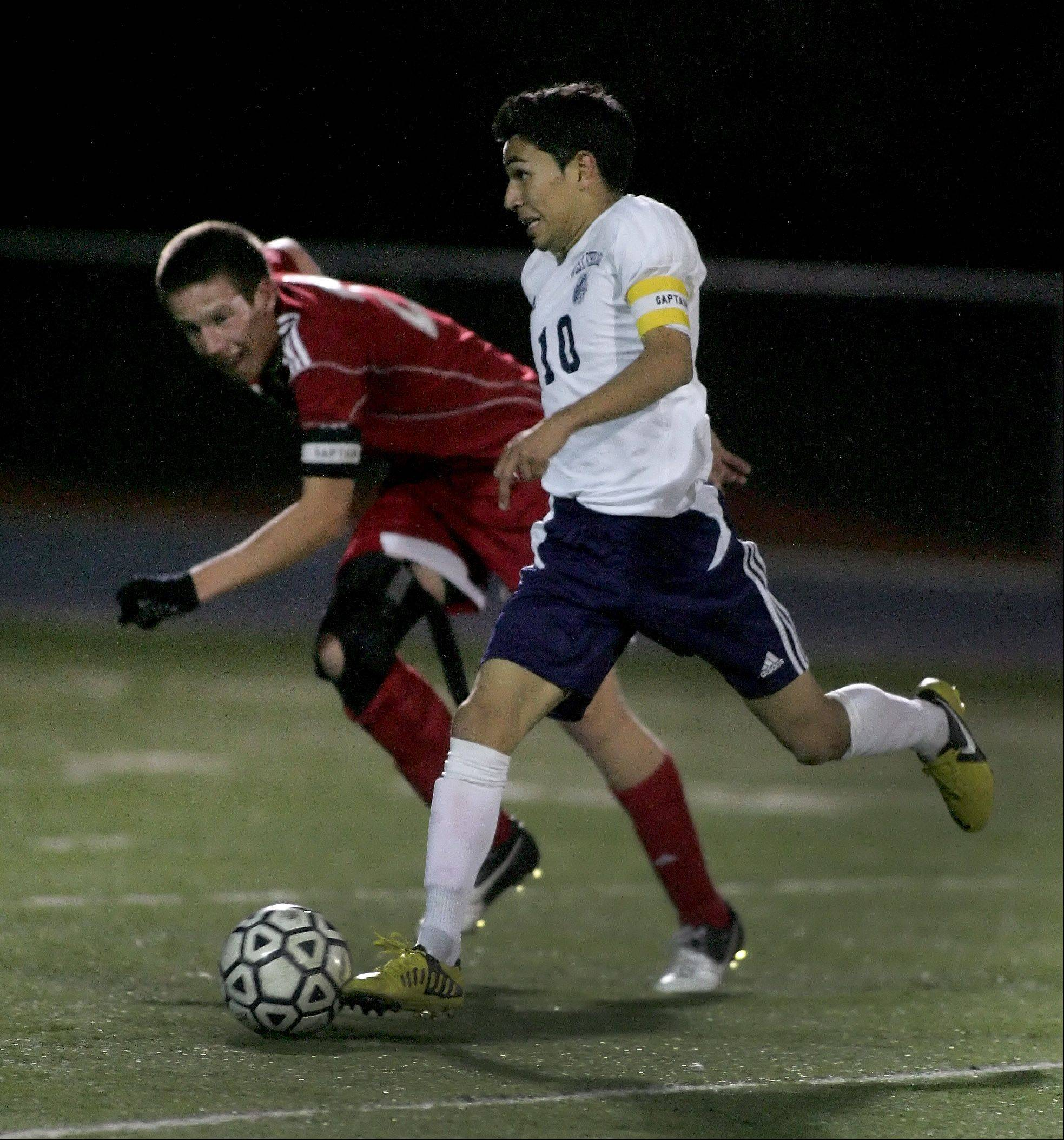 Diego Munoz of West Chicago moves the ball down the field and past Jack Patrick of Naperville Central in boys soccer action on Tuesday.