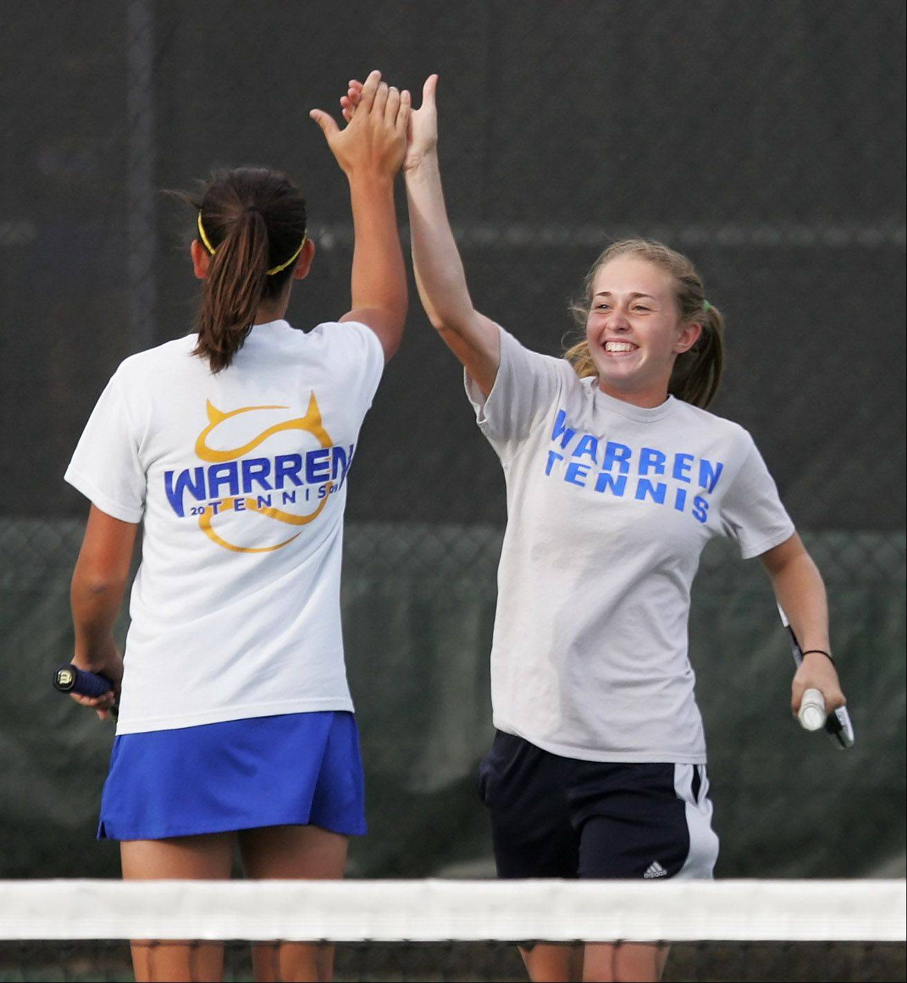 Warren doubles player Courtney Sunday, right, gives her partner, Mikayla Schultz, a high five after a point against Carmel Monday in Mundelein.