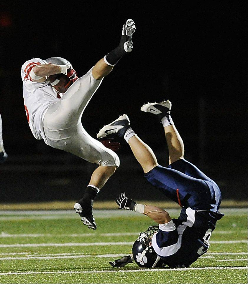 Palatine's Alex Nawrot flies over Conant's Kramer Brandt on a pass play during Friday's football game.