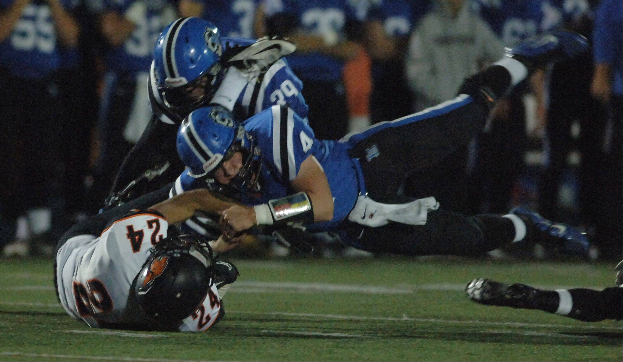 Lake Zurich's Noah Allgood, 4, lays into Libertyville's Austin Williams during Friday's football game in Lake Zurich.