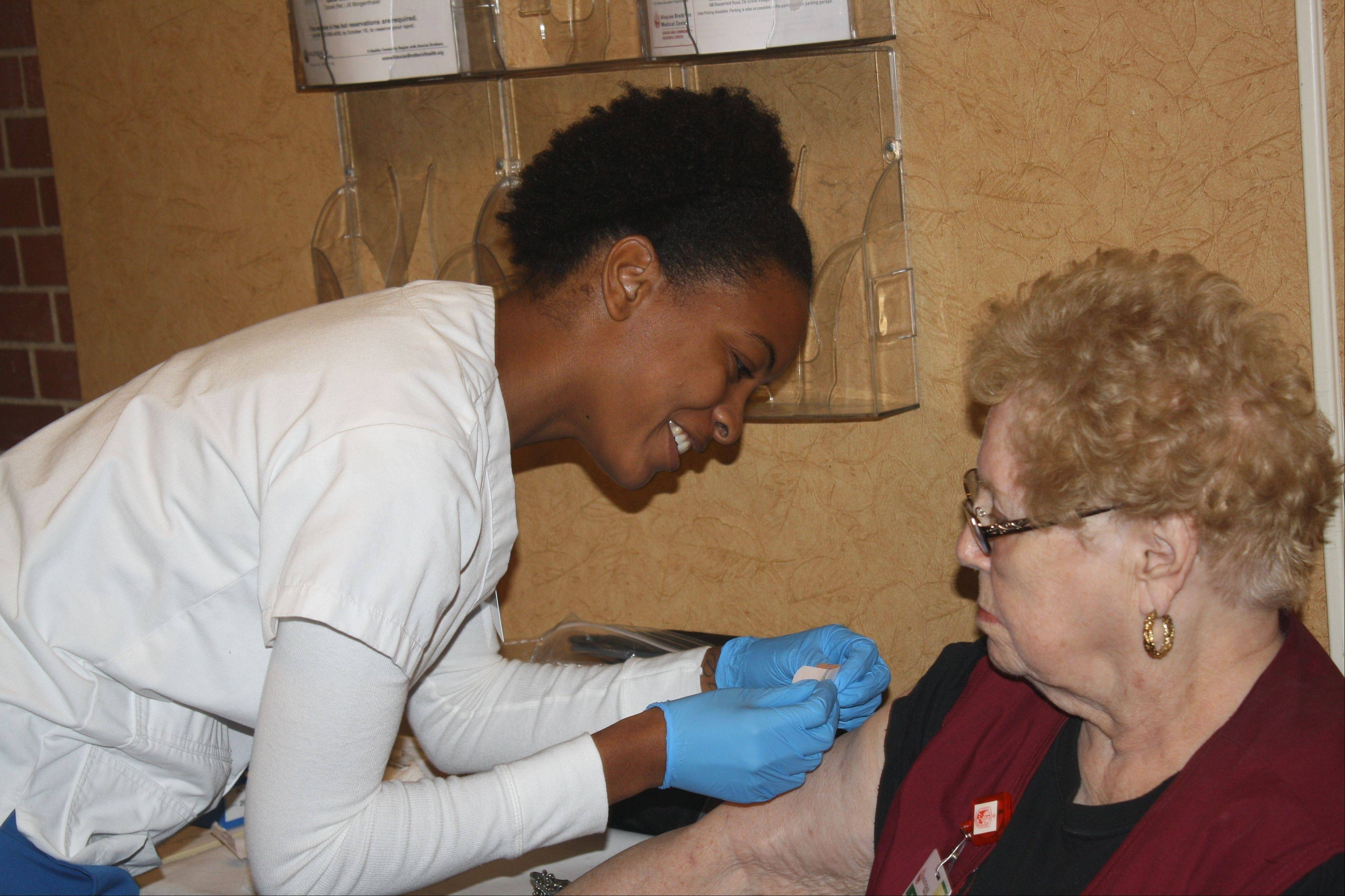 Harper College LPN student Tricia Williams administers a flu vaccine to a hospital volunteer at Alexian Brothers Medical Center.