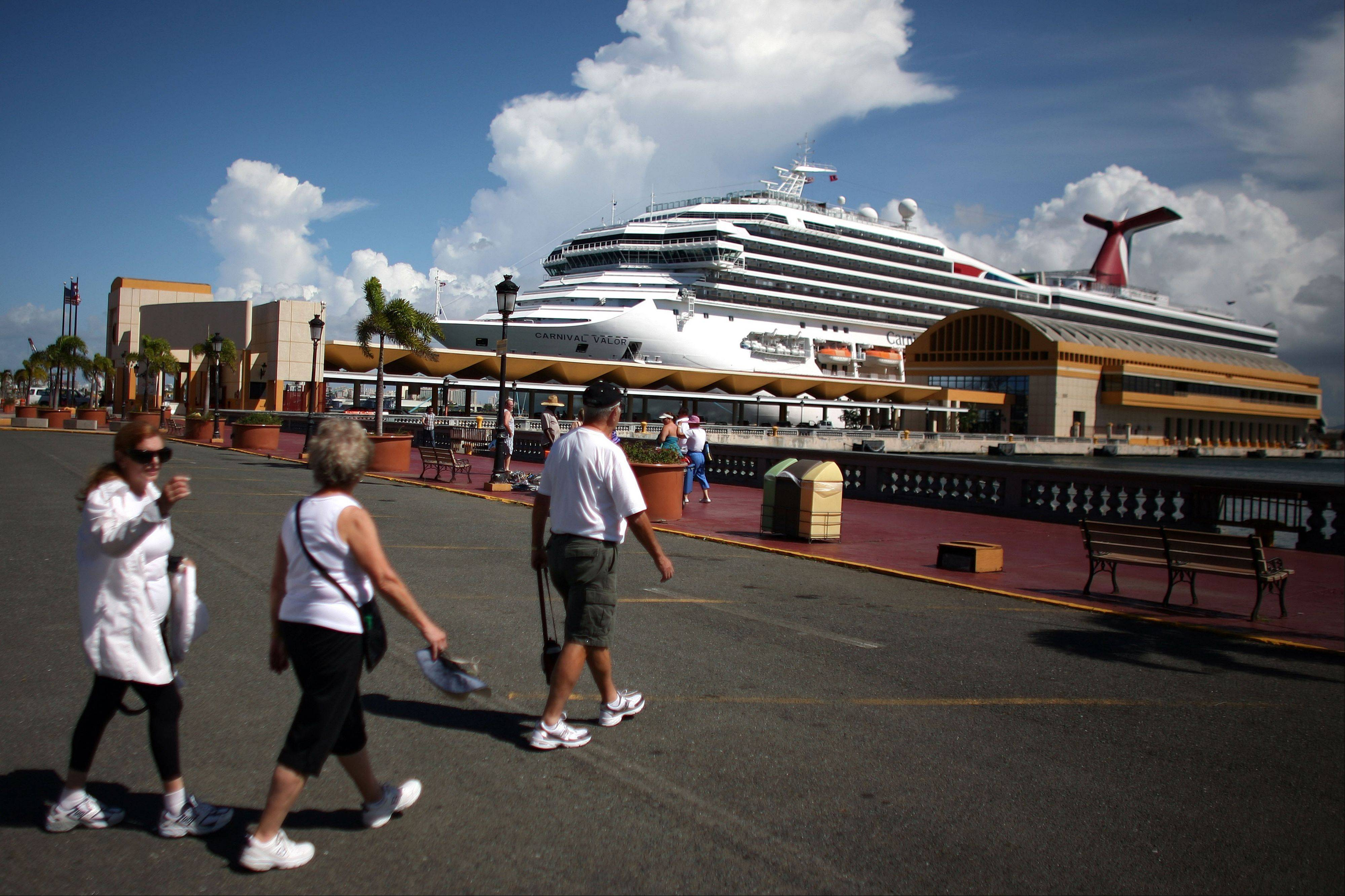 Tourists walk through a parking lot in front of a pier where a cruise ship is docked in Old San Juan, Puerto Rico. Trade groups say the flourishing cruise ship industry injects about $2 billion a year into the economies of the Caribbean, the worldís No. 1 cruise destination, but critics complain that it produces relatively little local revenue because so many passengers dine, shop and purchase heavily marked-up shore excursions on the boats or splurge at international chain shops on the piers.