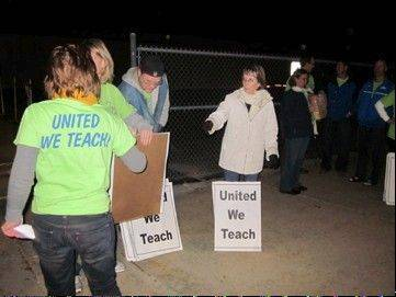 Geneva teachers turn their picket signs in at the end of a protest Tuesday night before a Geneva school board meeting.