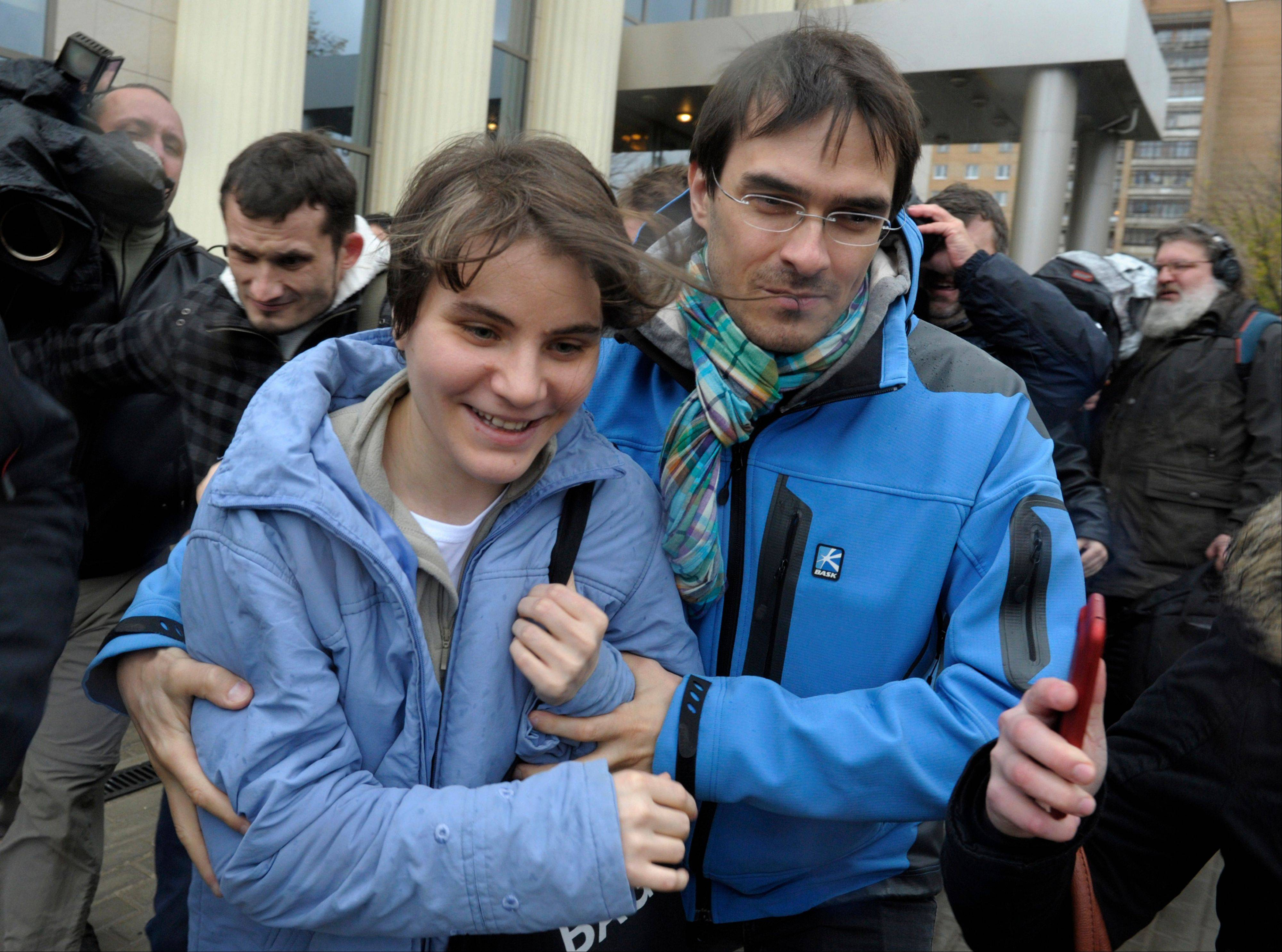 Freed feminist punk group Pussy Riot member Yekaterina Samutsevich, left, leaves a court in Moscow, Wednesday Oct. 10, 2012. A Moscow appeals court on Wednesday unexpectedly freed Yekaterina Samutsevich of the jailed Pussy Riot group, but upheld the two-year prison sentence for the two others jailed for an irreverent protest against President Vladimir Putin.