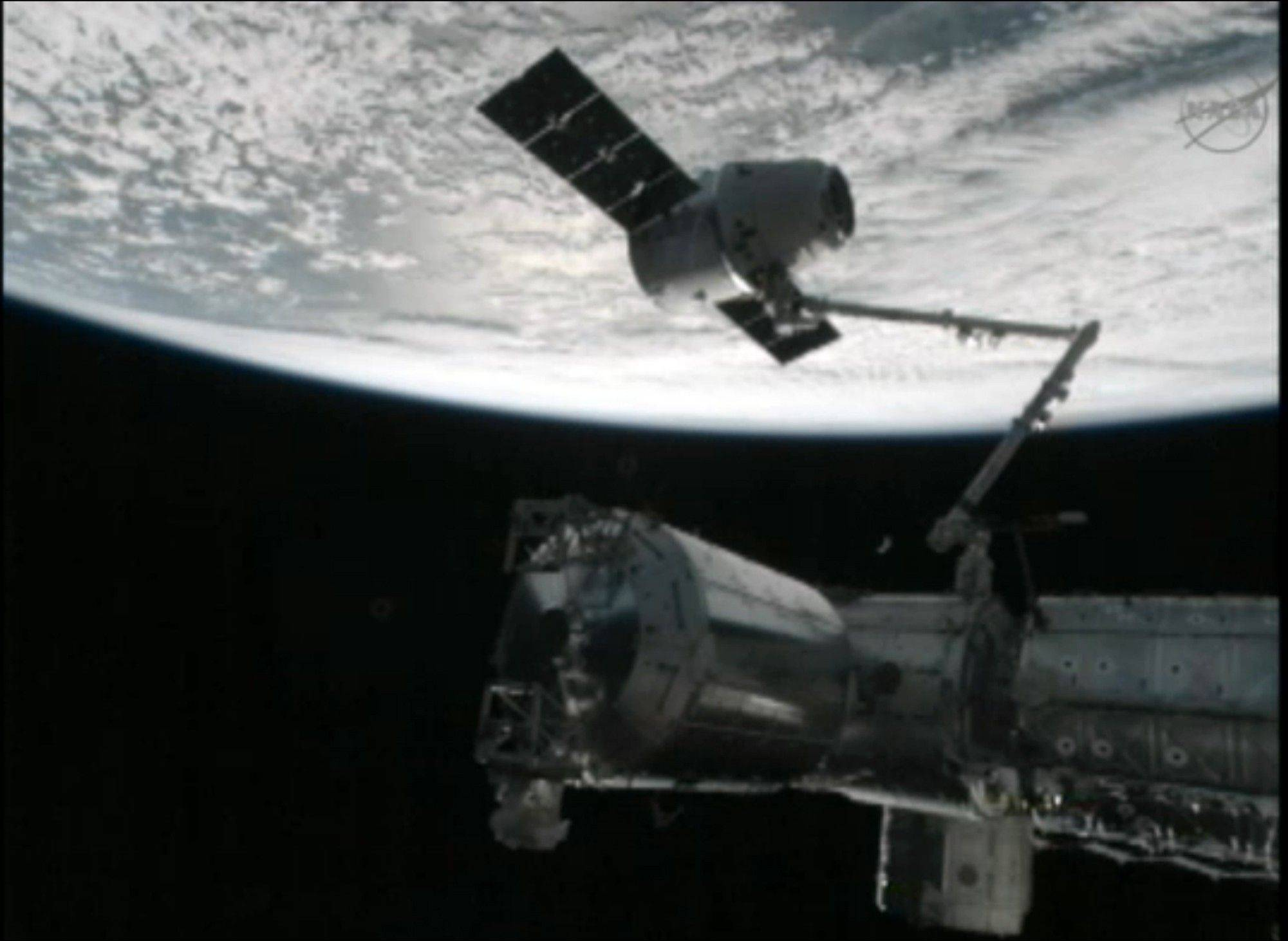This image from NASA-TV shows the capture of the Dragon capsule by a robot arm on the International Space Station as they passed over the South Atlantic Ocean early Wednesday Oct. 10, 2012. It's the first official delivery by the California-based SpaceX company under a $1.6 billion contract with NASA. The contract calls for 12 such shipments.