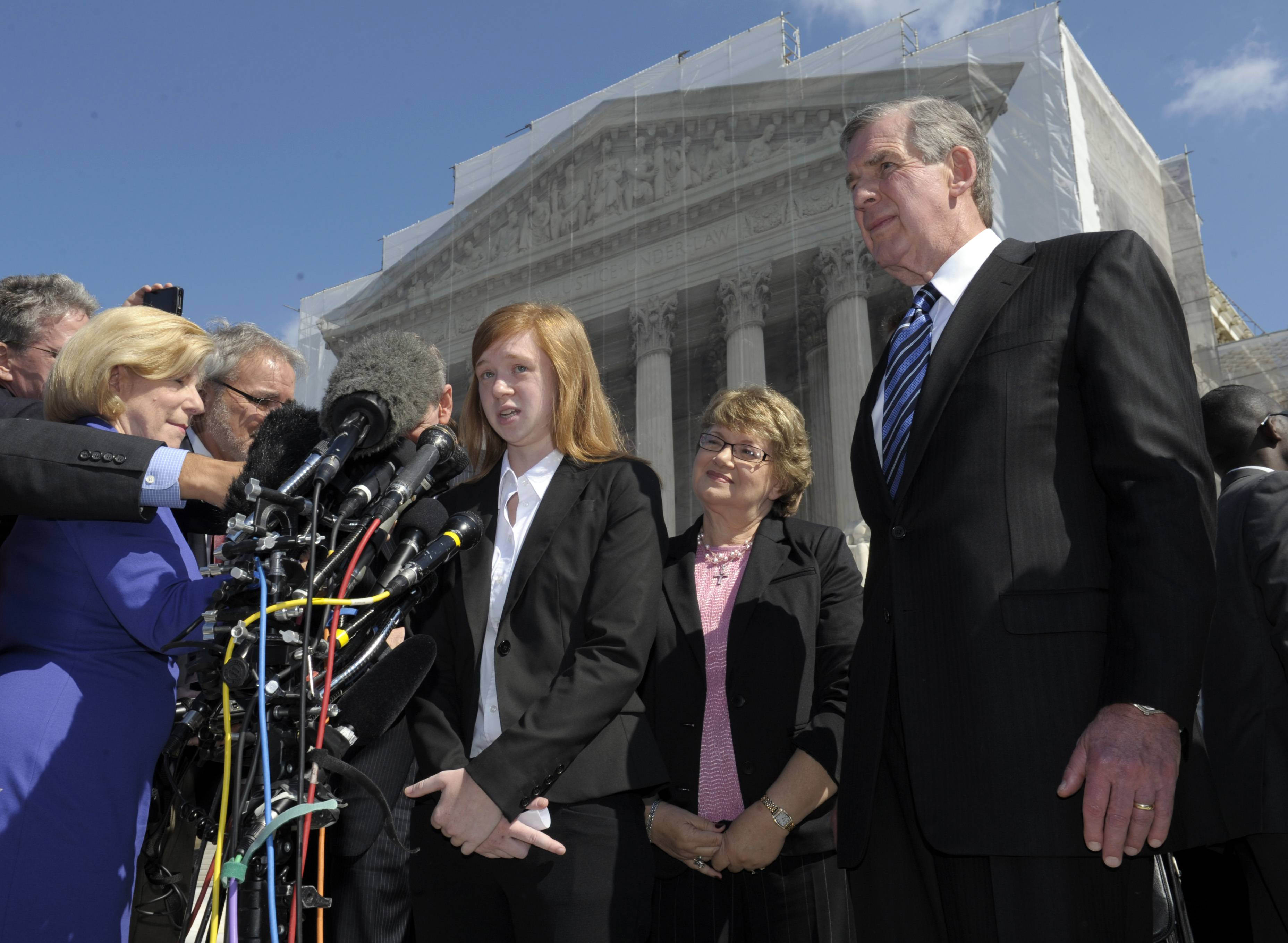 Abigail Fisher, the Texan involved in the University of Texas affirmative action case, accompanied by her attorney Bert Rein, right, talks to reporters Wednesday outside the Supreme Court in Washington. The Supreme Court is taking up a challenge to a University of Texas program that considers race in some college admissions. The case could produce new limits on affirmative action at universities, or roll it back entirely.