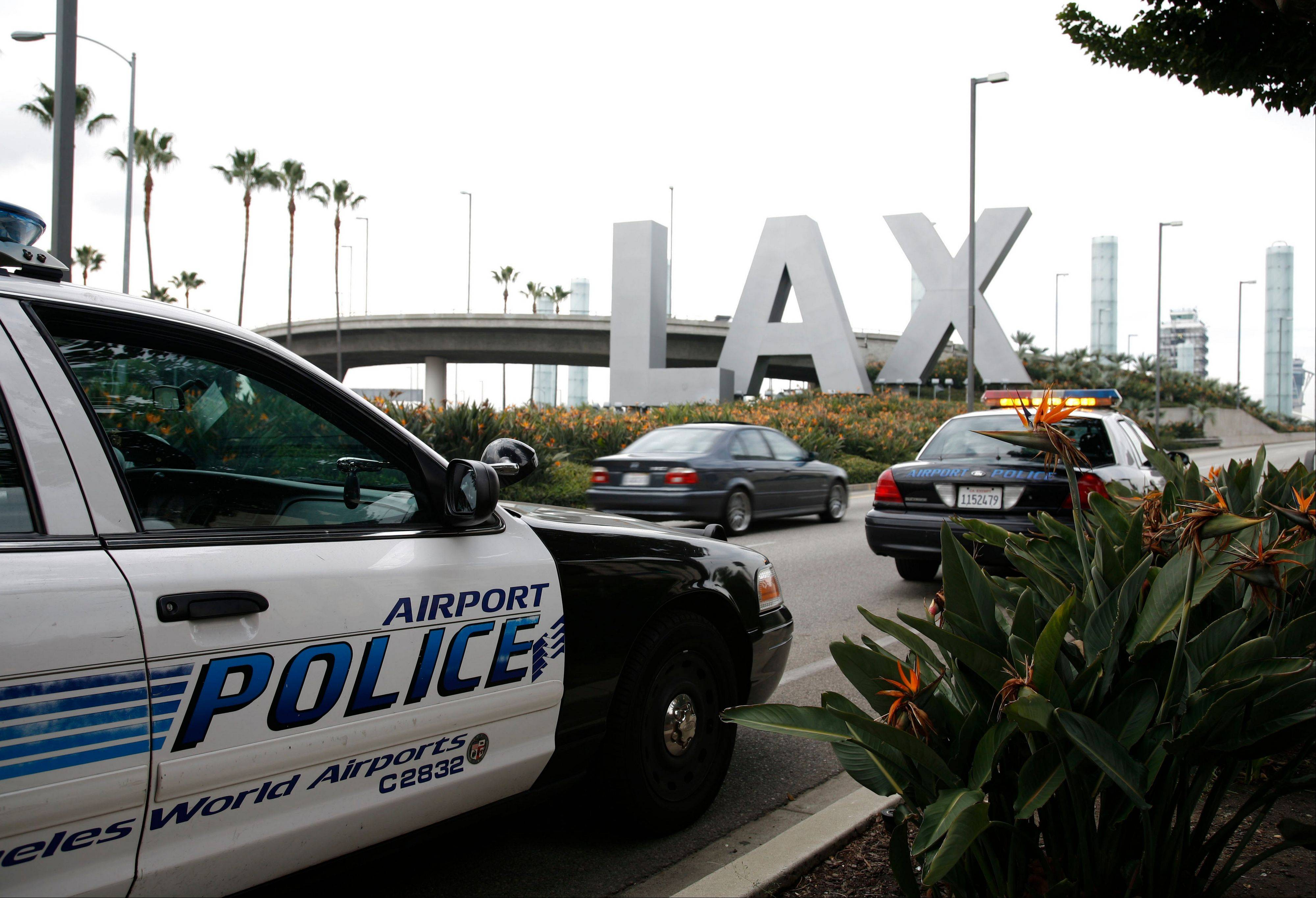 Airport police monitor the entrance of Los Angeles International Airport in Los Angeles. Yongda Huang Harris, 28, flying from Japan to Boston, was arrested Friday, Oct. 5, 2012, during a stopover at Los Angeles International Airport, wearing a bulletproof vest and flame-resistant pants, and traveling with a suitcase full of weapons, leg irons, a smoke grenade, a gas mask and a biohazard suitd, U.S. Immigration and Customs Enforcement officials said.
