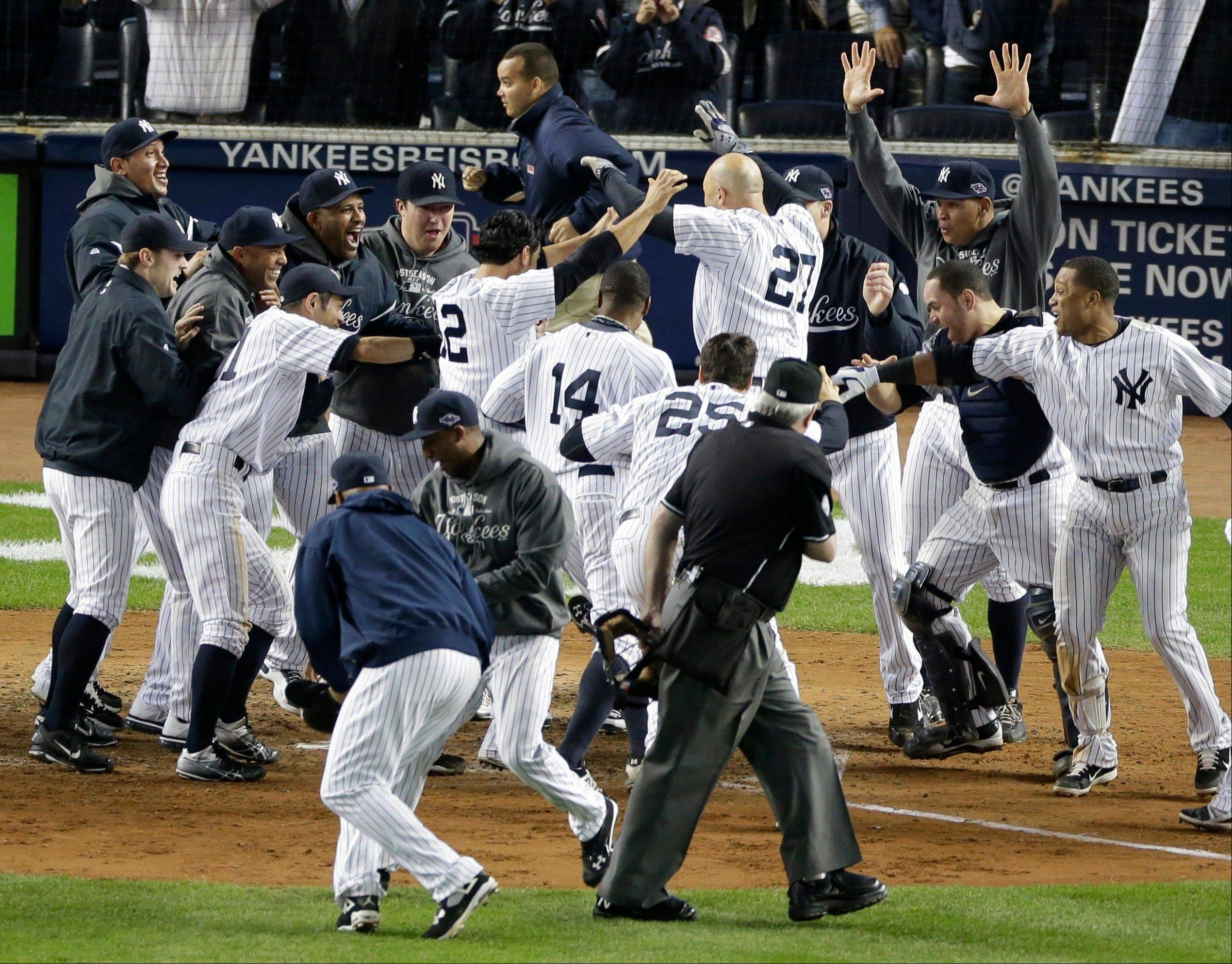 New York Yankees' Raul Ibanez (27) is mobbed by teammates at home plate Wednesday after he hit the game-winning home run in the 12th inning in Game 3 of the American League division baseball series. The Yankees beat the Baltimore Orioles 3-2.