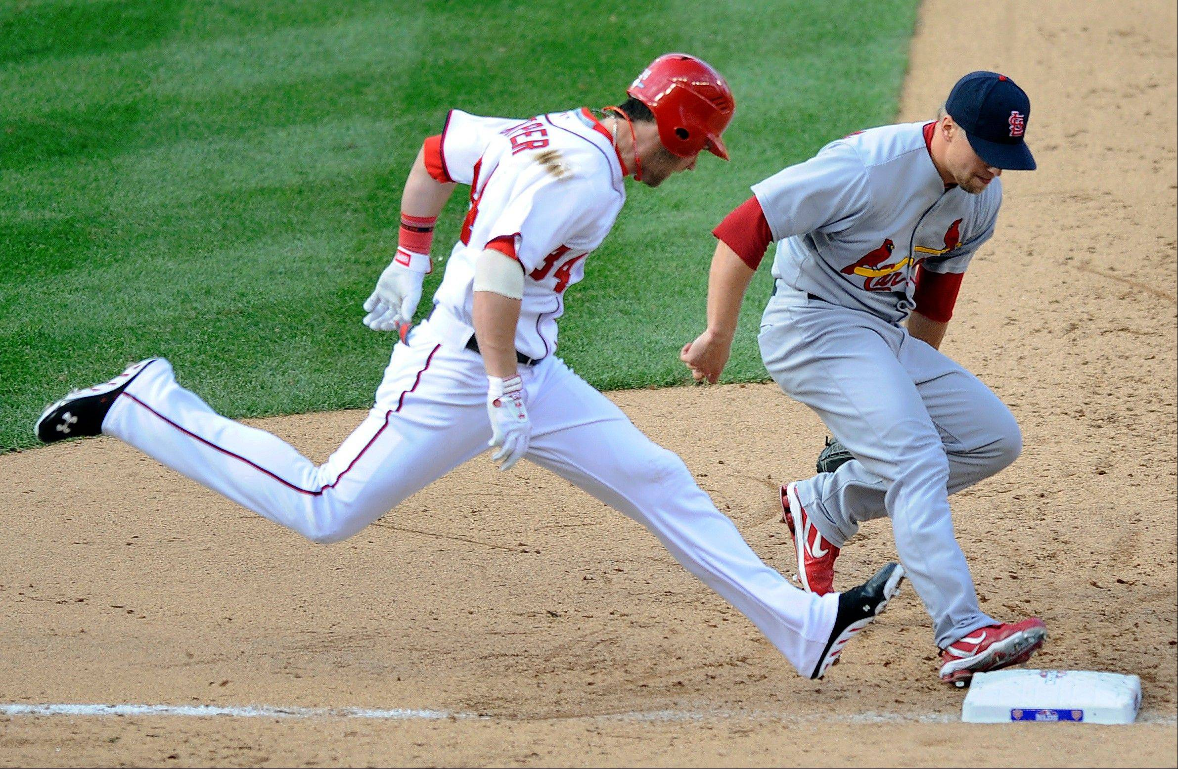 St. Louis Cardinals relief pitcher Trevor Rosenthal beats the Washington Nationals' Bryce Harper to first base for an out Wednesday during the seventh inning of Game 3 in Washington.